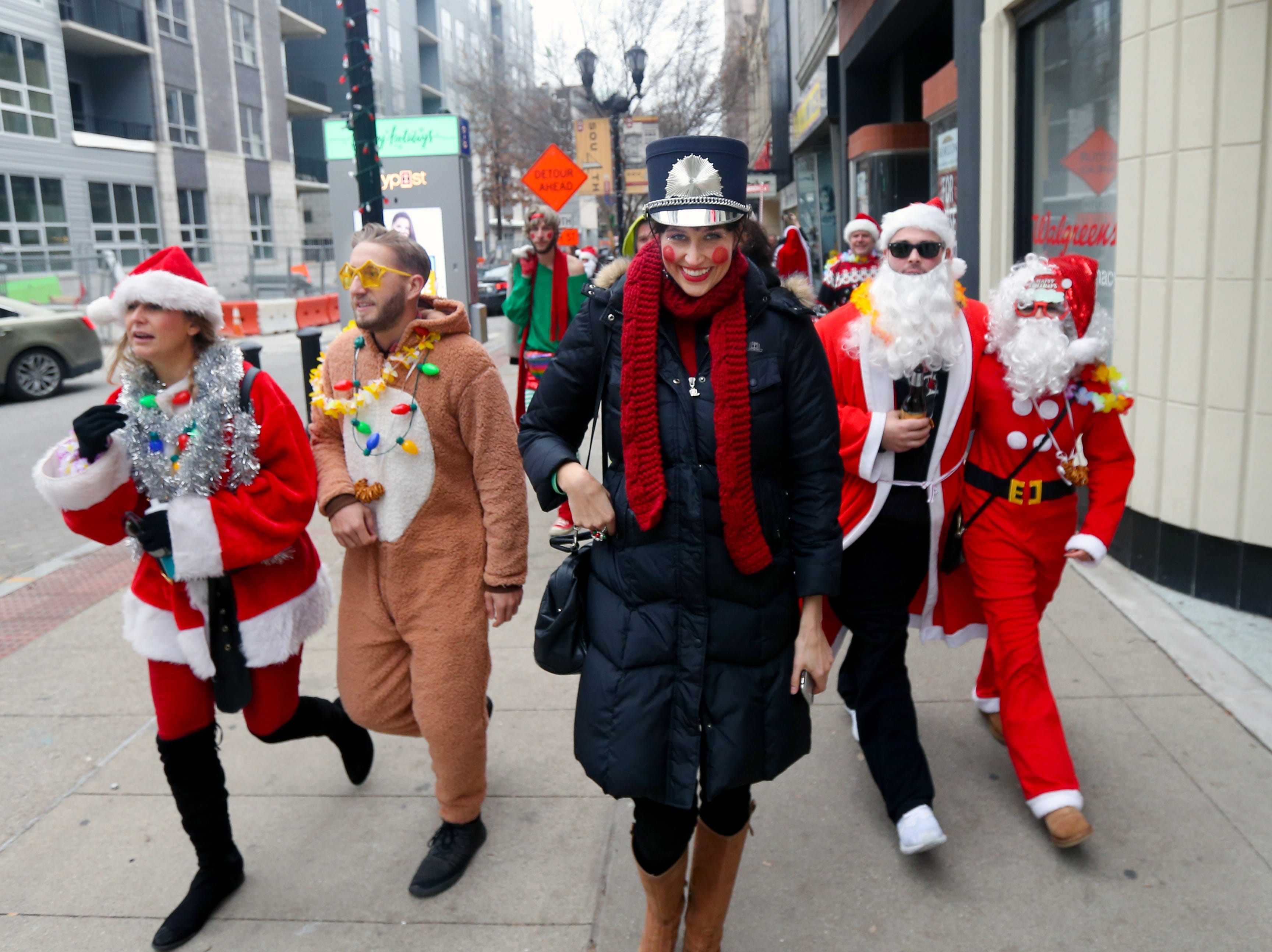 Marge Royston leads a part of the Louisville'e SantaCon crowd to the next location. Dec. 8, 2018