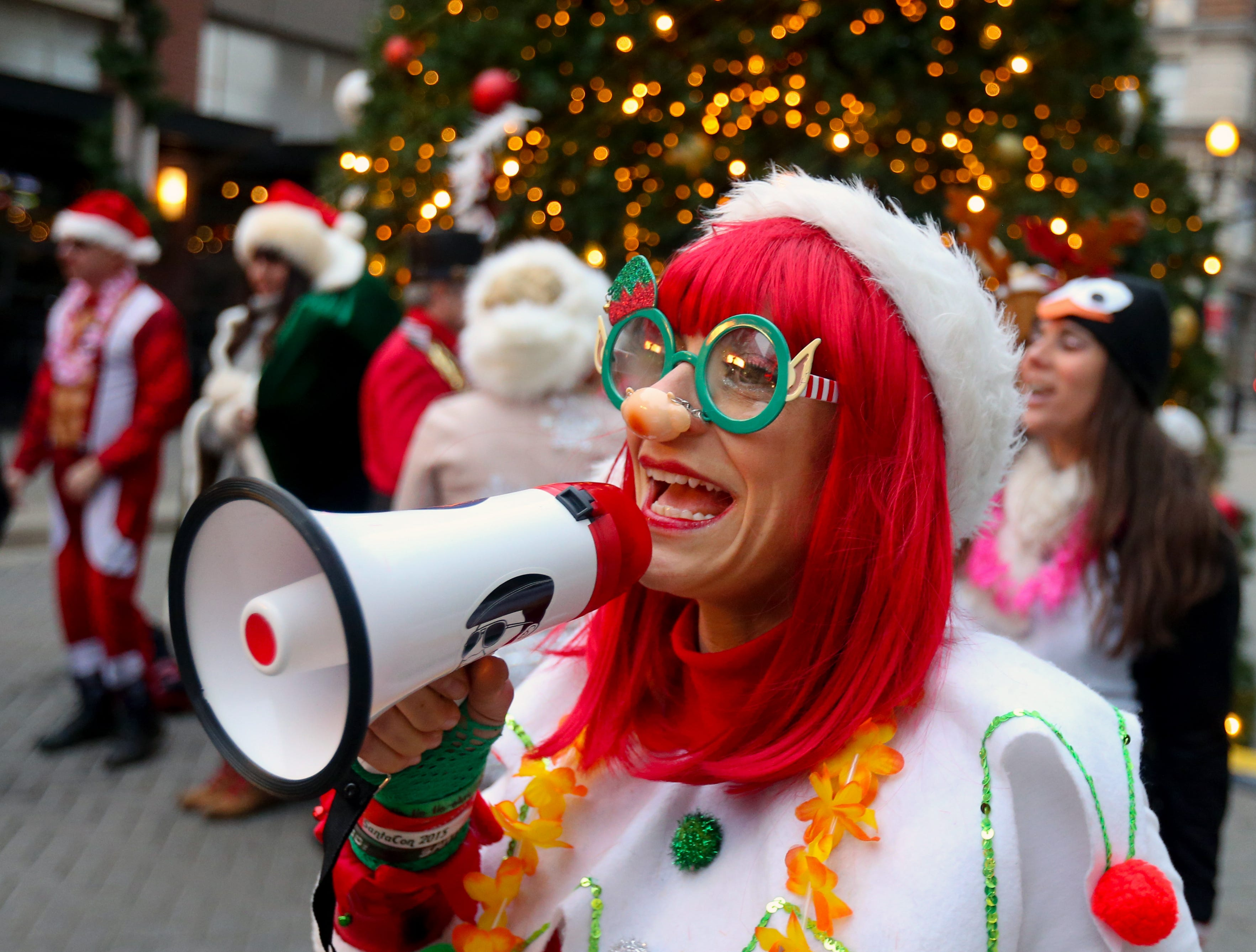 Jenna Ankenbrand, one of Santa's workers, leads the SantaCon crowd to the next location.    Dec. 8, 2018