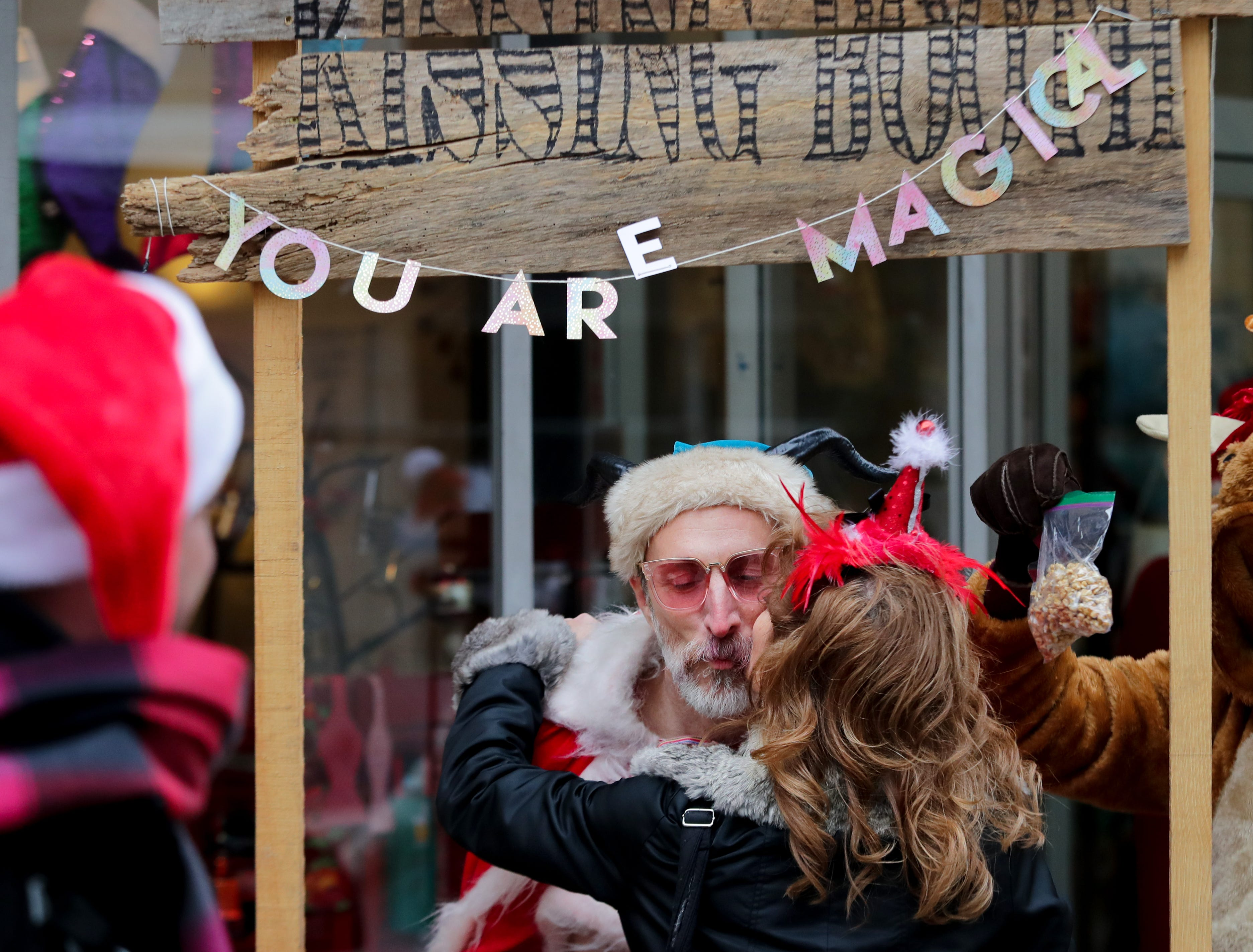 J.D. Dotson, one of Santa's workers, occupies the Kissing Booth at one of the SantaCon's stops.    Dec. 8, 2018