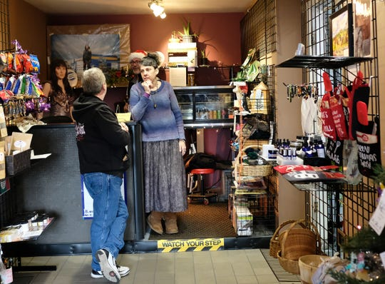 Patti Akley, manager of the Lansing Eastside Gateway talks to a customer Sunday, Dec. 9, 2018.