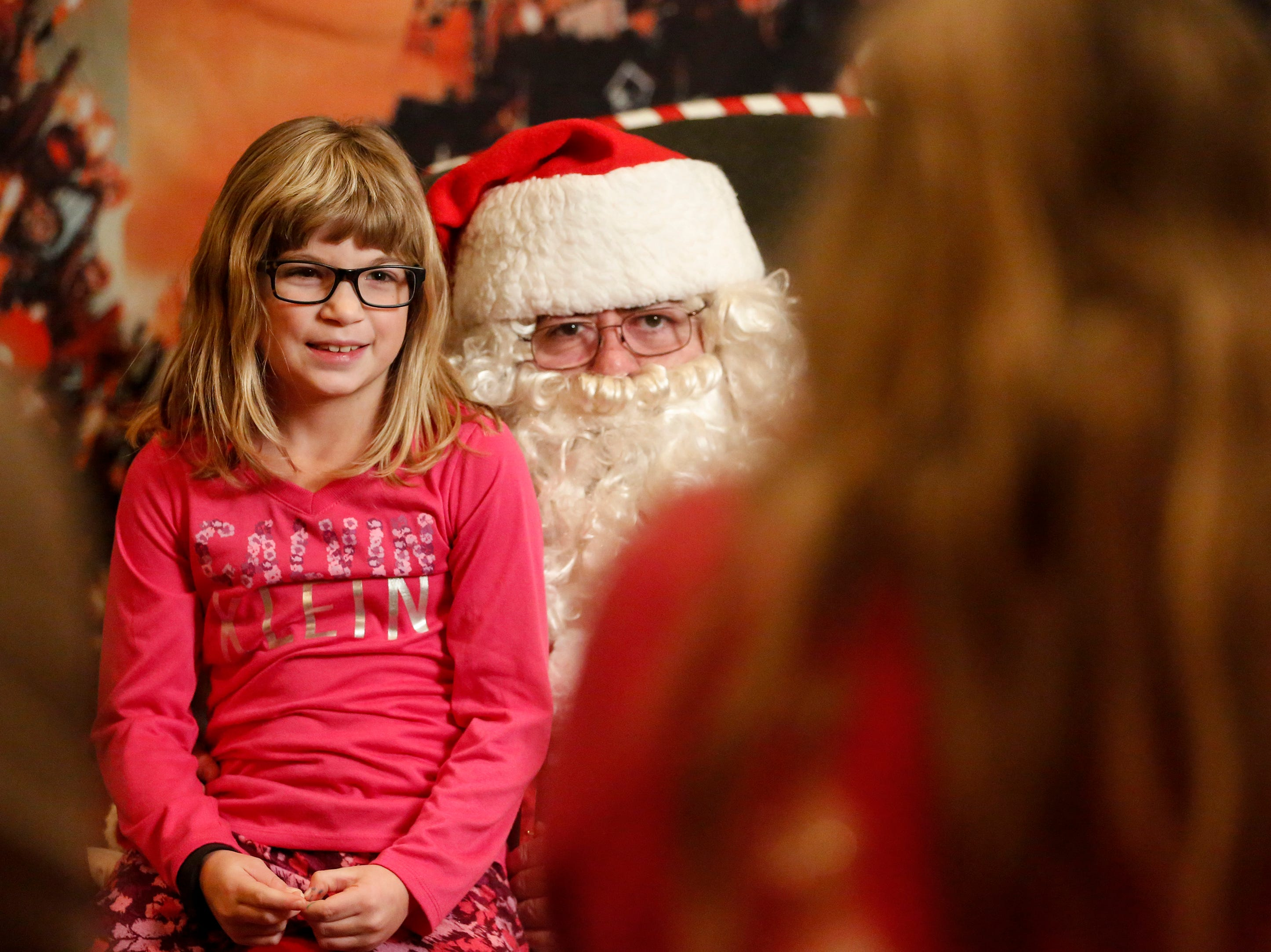 A child poses on Santa's lap for a photo at Santa's North Pole at the Holiday Inn Saturday, December 8, 2018, in Manitowoc, Wis. Joshua Clark/USA TODAY NETWORK-Wisconsin