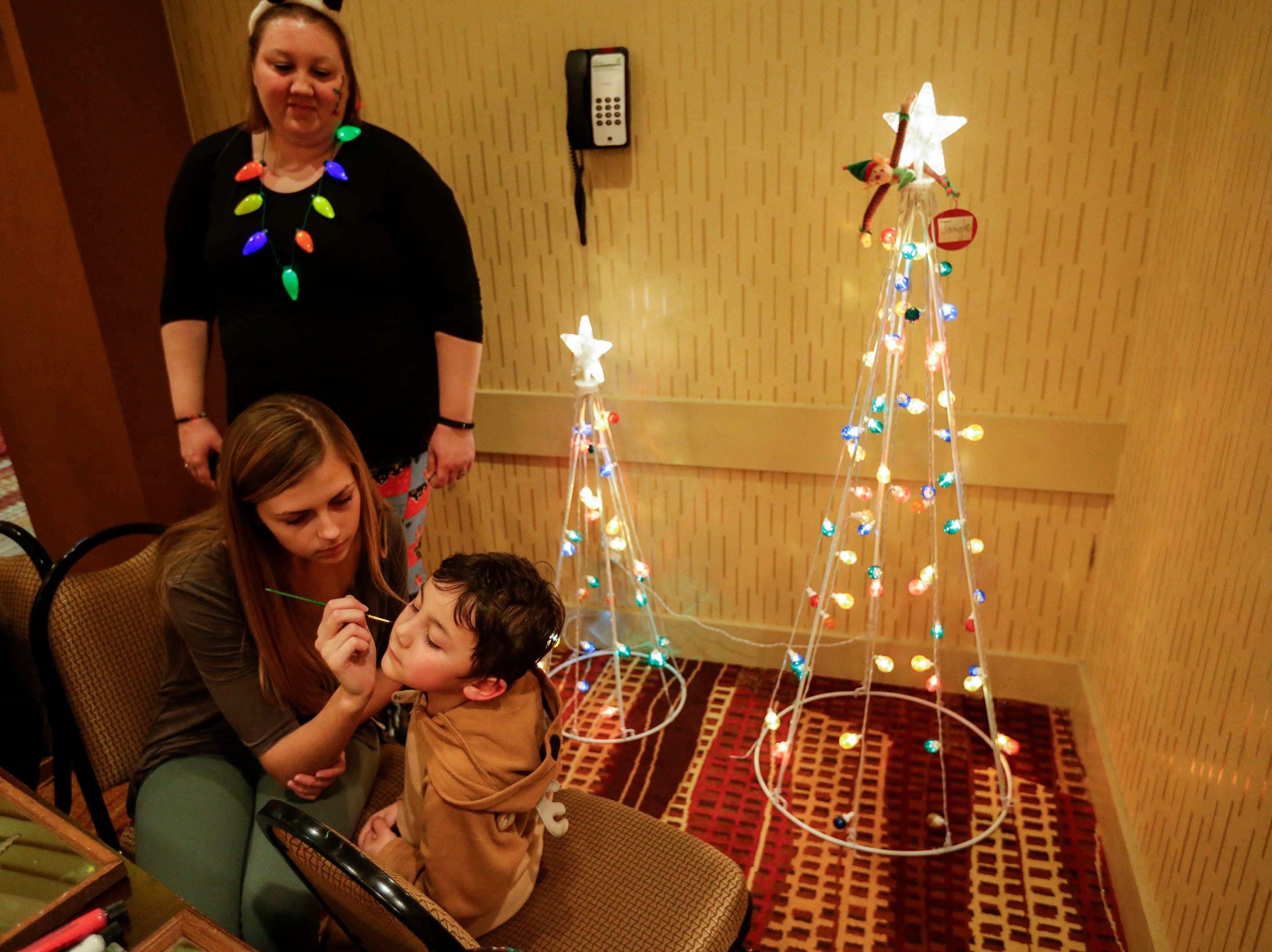 Jace Buchanan, 4, of Neenah, gets his face painted by Taylor Brown at Santa's North Pole at the Holiday Inn Saturday, December 8, 2018, in Manitowoc, Wis. Joshua Clark/USA TODAY NETWORK-Wisconsin