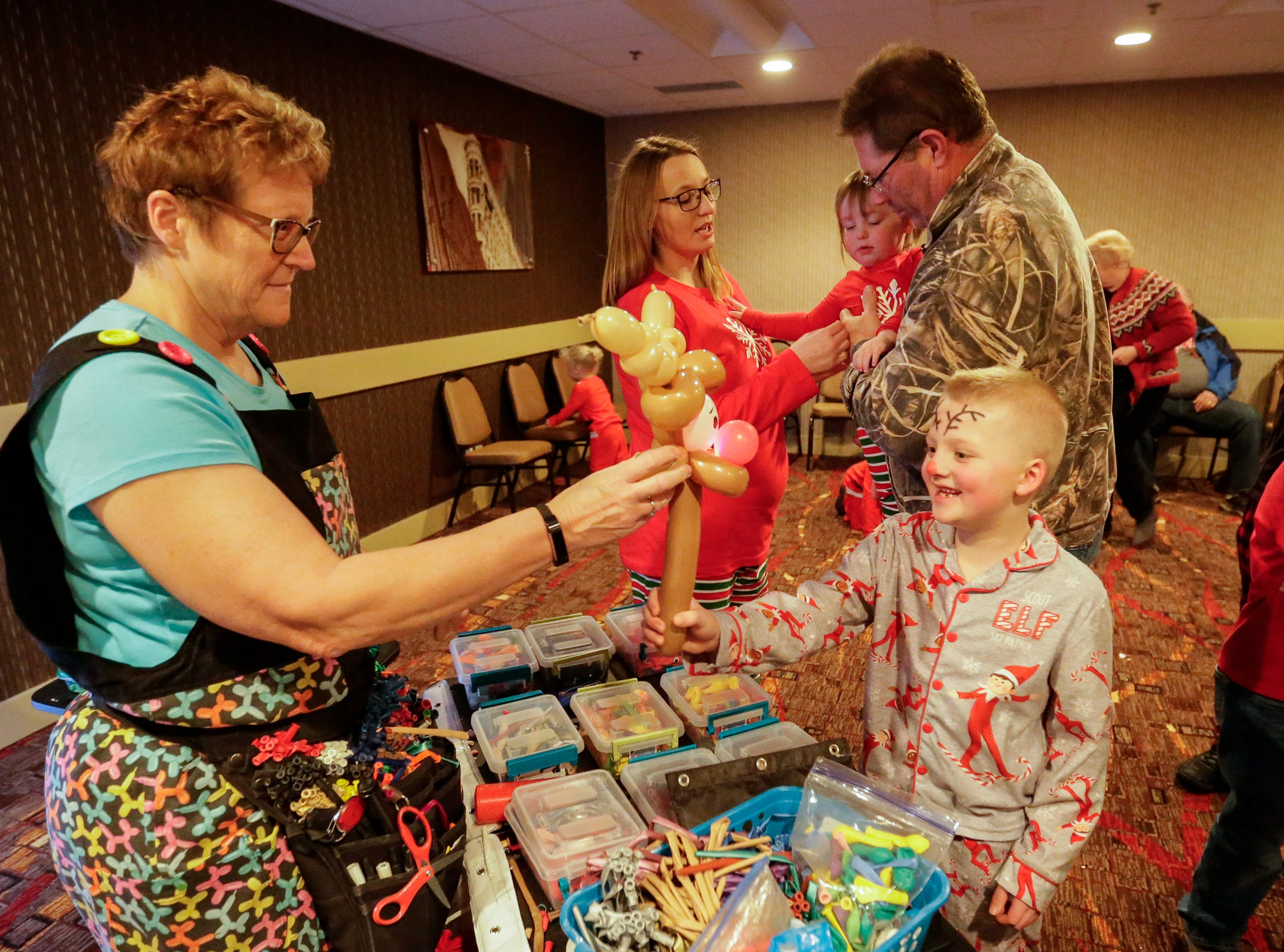 Jax Arkens, 7, of Mishicot, takes a Rudolph the Red Nosed Reindeer ballon animal at Santa's North Pole at the Holiday Inn Saturday, December 8, 2018, in Manitowoc, Wis. Joshua Clark/USA TODAY NETWORK-Wisconsin