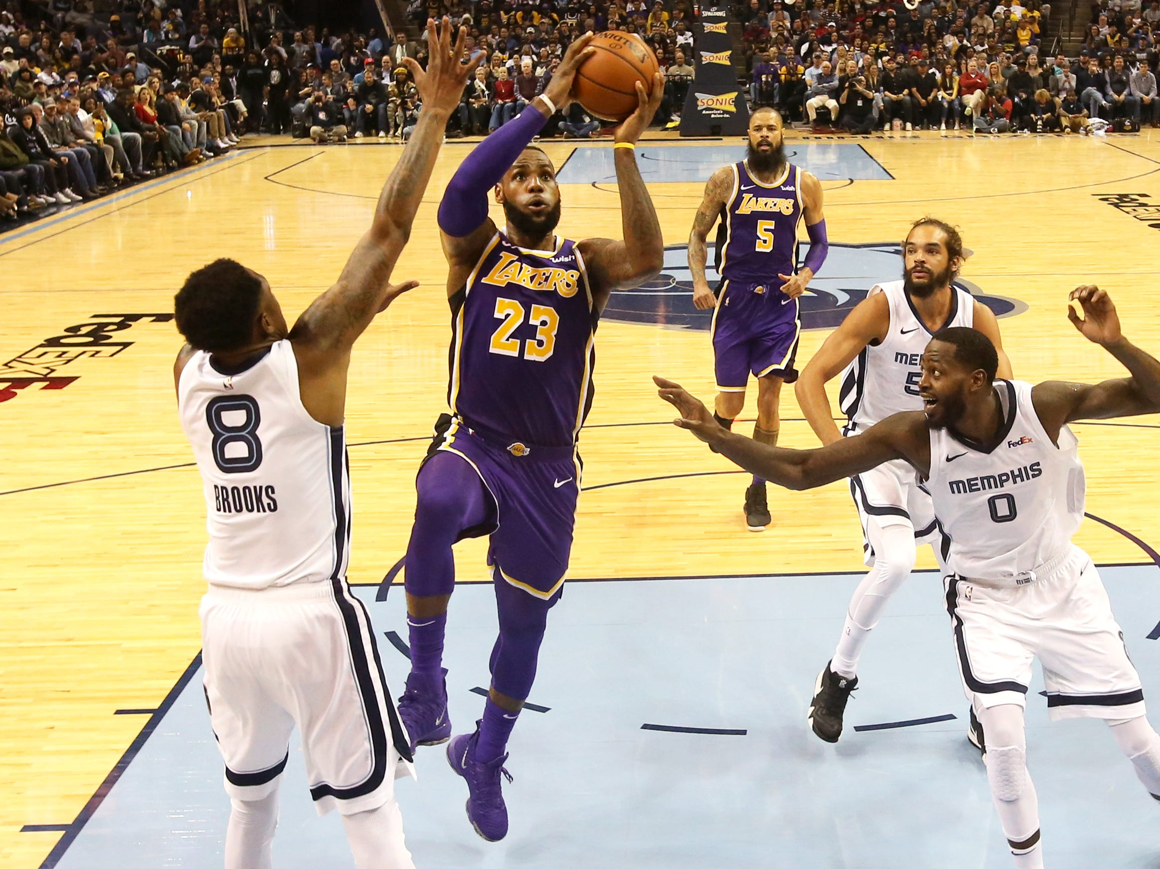 Los Angeles Lakers forward LaBron James lays the ball up past Memphis Grizzlies guard MarShon Brooks duirng their game at the FedExForum on Saturday, Dec. 8, 2018.