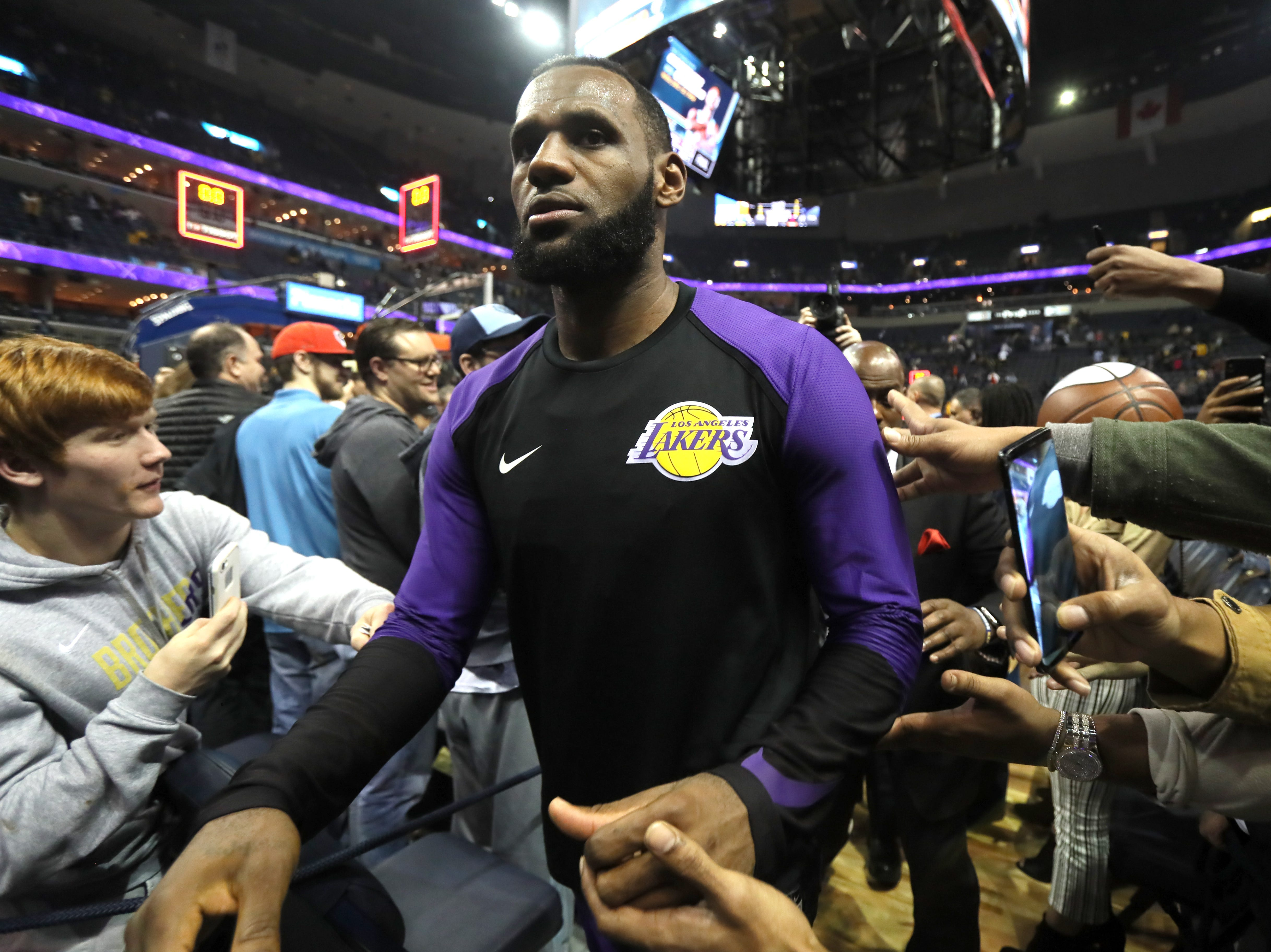 Los Angeles Lakers forward LeBron James high-fives fans as he walks off the FedExForum floor after beating the Memphis Grizzlies on Saturday, Dec. 8, 2018.