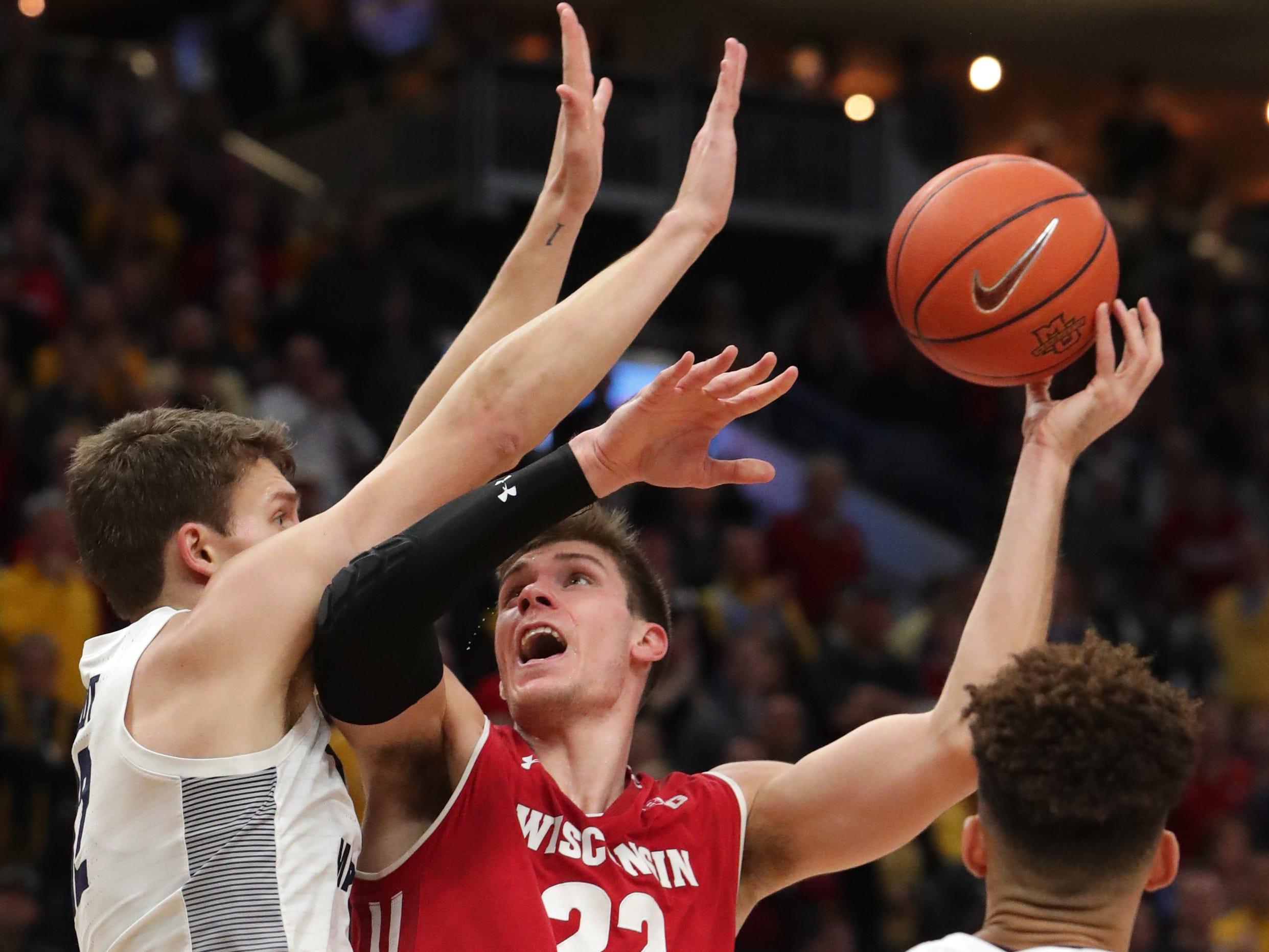 Wisconsin forward Ethan Happ (22) is tested by Marquette center Matt Heldt.