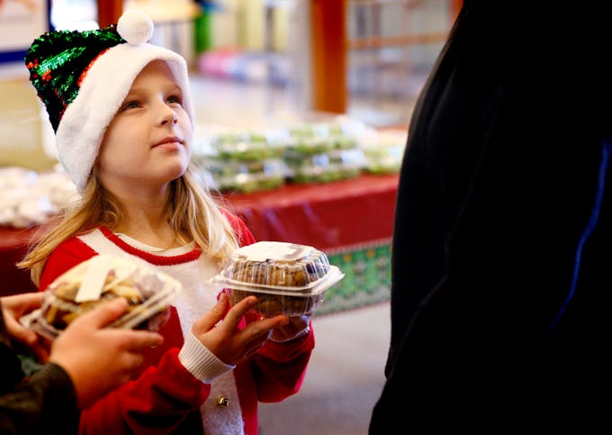 Brooke Babich, 8, brings her cookie selection for final purchase approval during the Redeemer United Church of Christ's annual Christmas Cookie Sale in Menomonee Falls on Dec. 8.