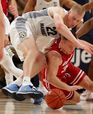 Marquette forward Joey Hauser (22) and Wisconsin guard Brad Davison scramble for the ball Saturday.