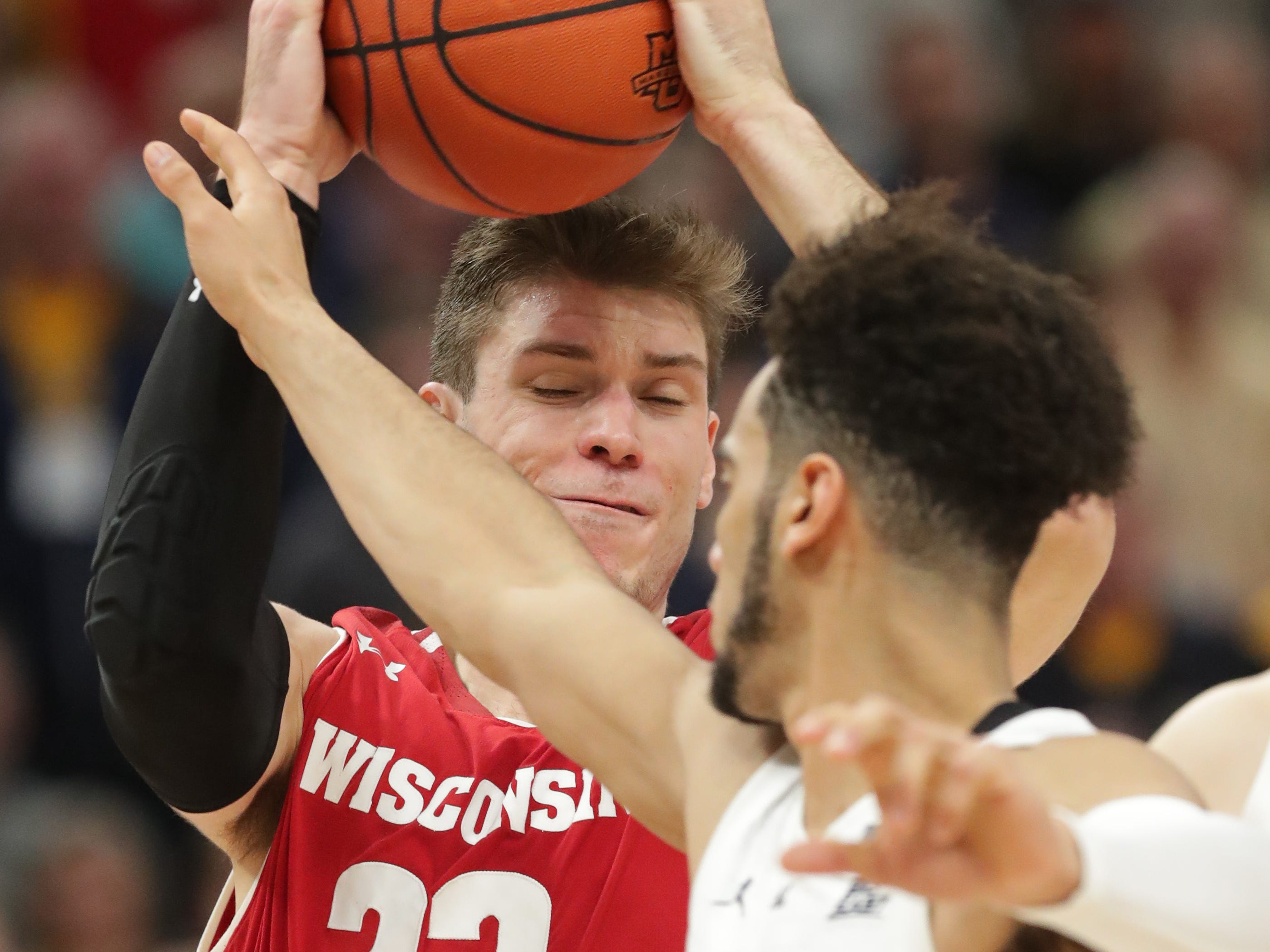 Wisconsin forward Ethan Happ is defended by Marquette guard Markus Howard.