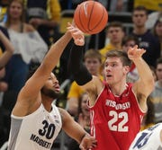 Marquette's Ed Morrow (left) defends Wisconsin forward Ethan Happ.