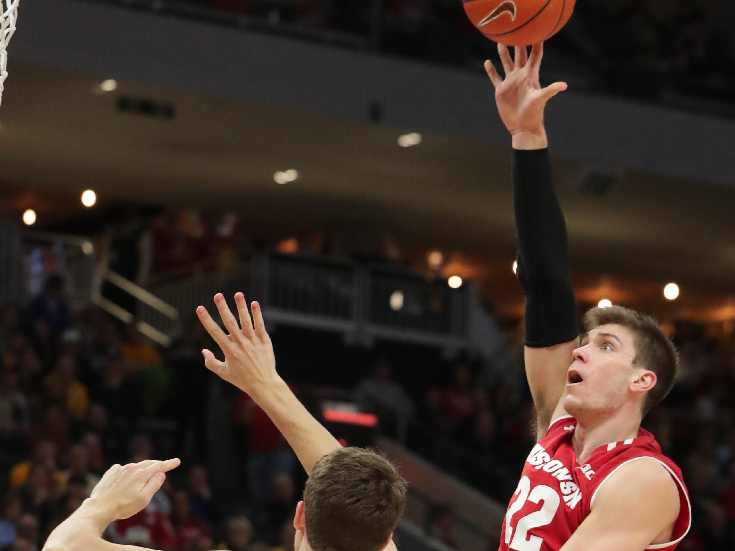 Wisconsin forward Ethan Happ shoots over Marquette center Matt Heldt.