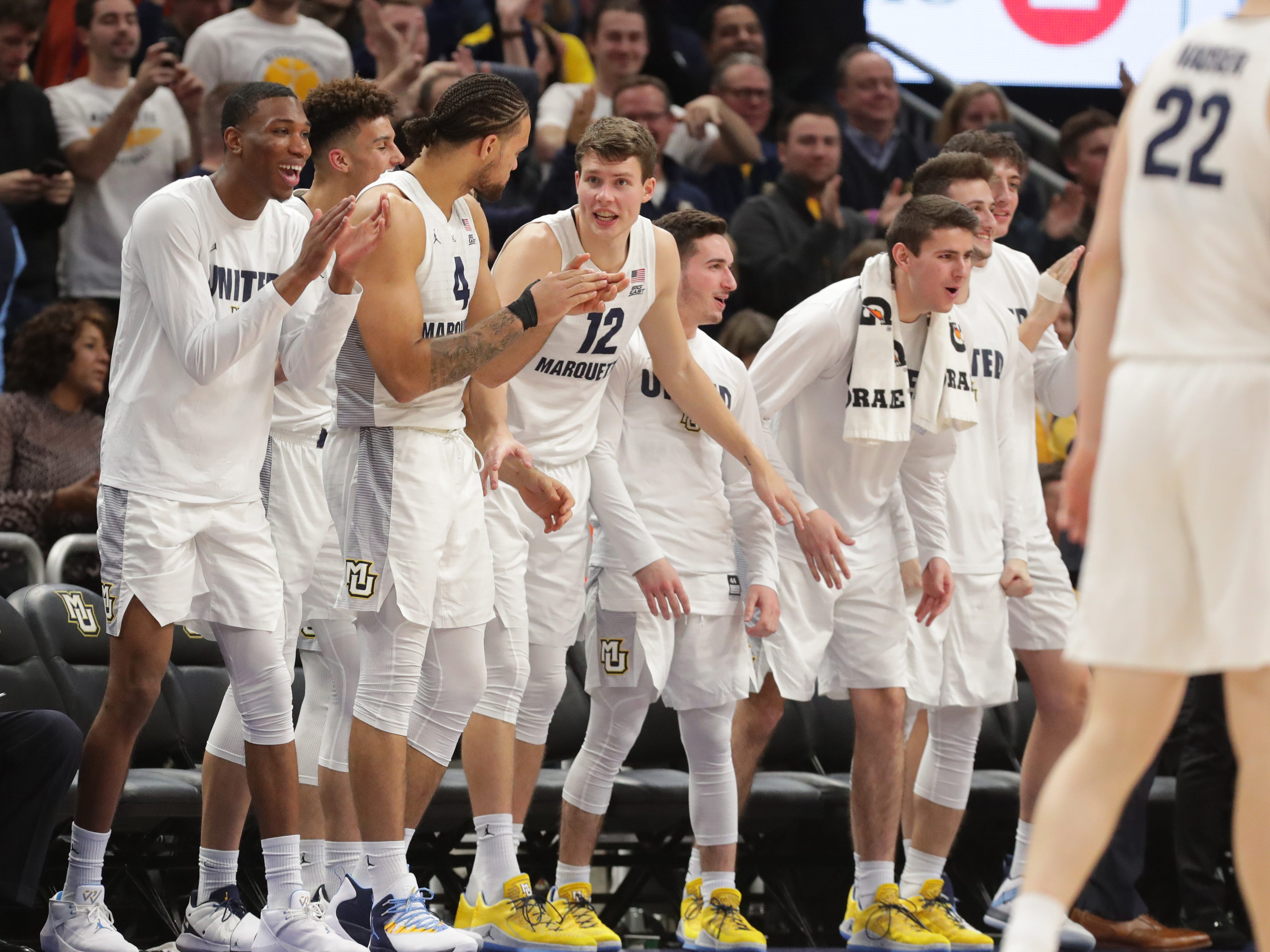 The Marquette bench cheers after guard Markus Howard is fouled during overtime.