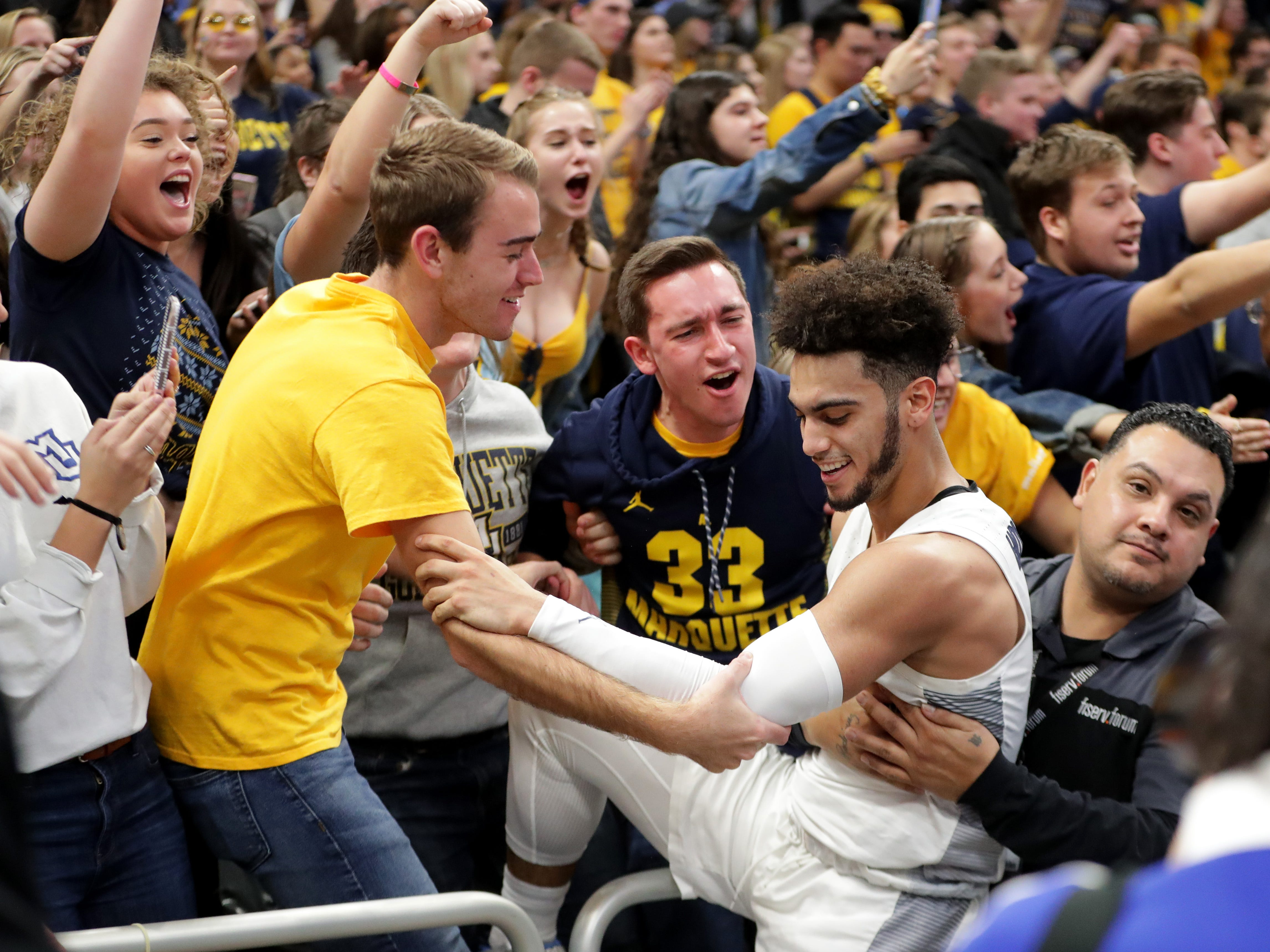 Marquette guard Markus Howard celebrates with fans after the game Saturday at Fiserv Forum in Milwaukee.
