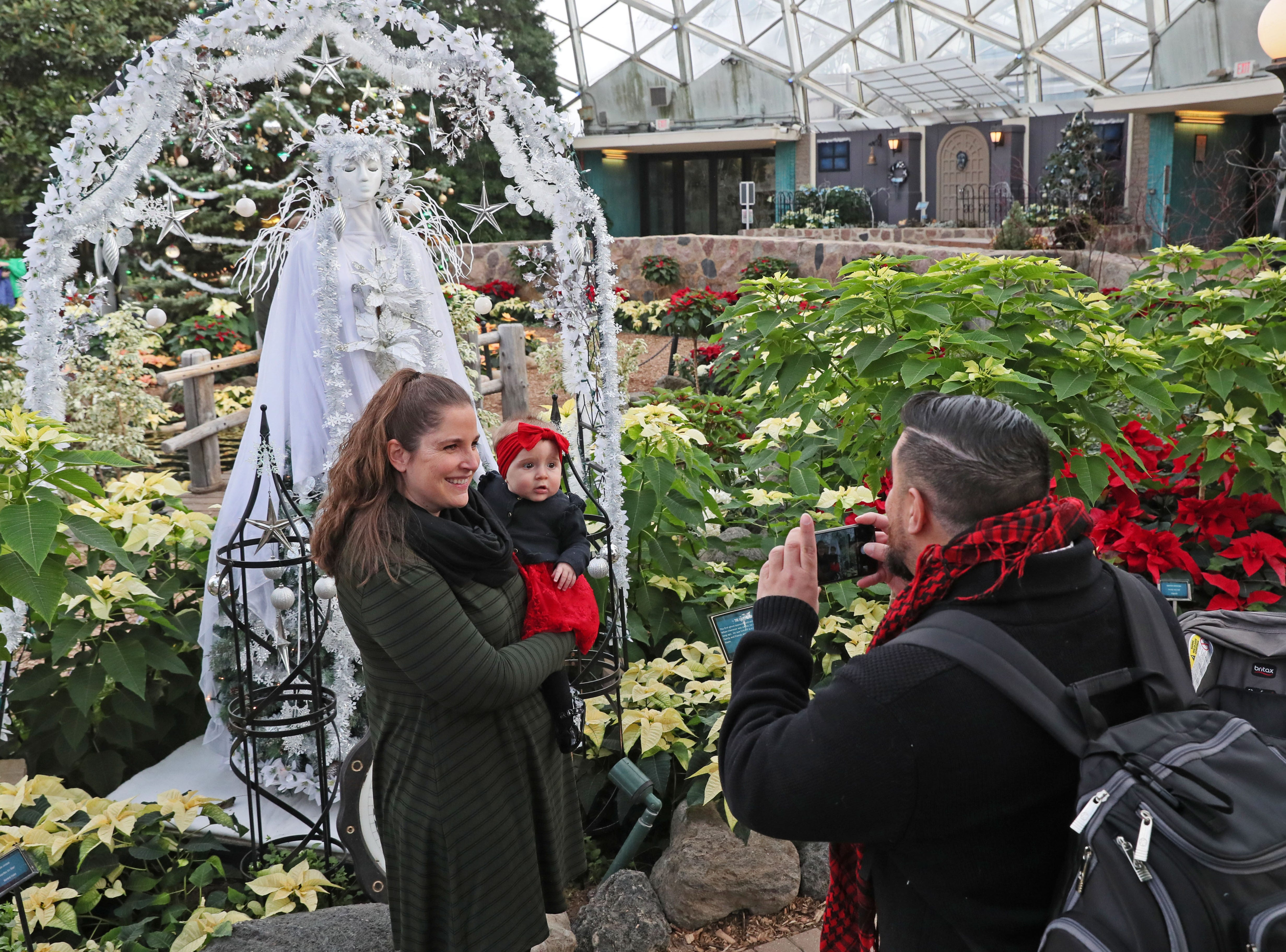 """Jamie Gonzalez holds her 6-month-old daughter Alejandrina in front of the """"Ghost of Christmas Past"""" as her husband Jason Gonzalez of Milwaukee photographed them."""