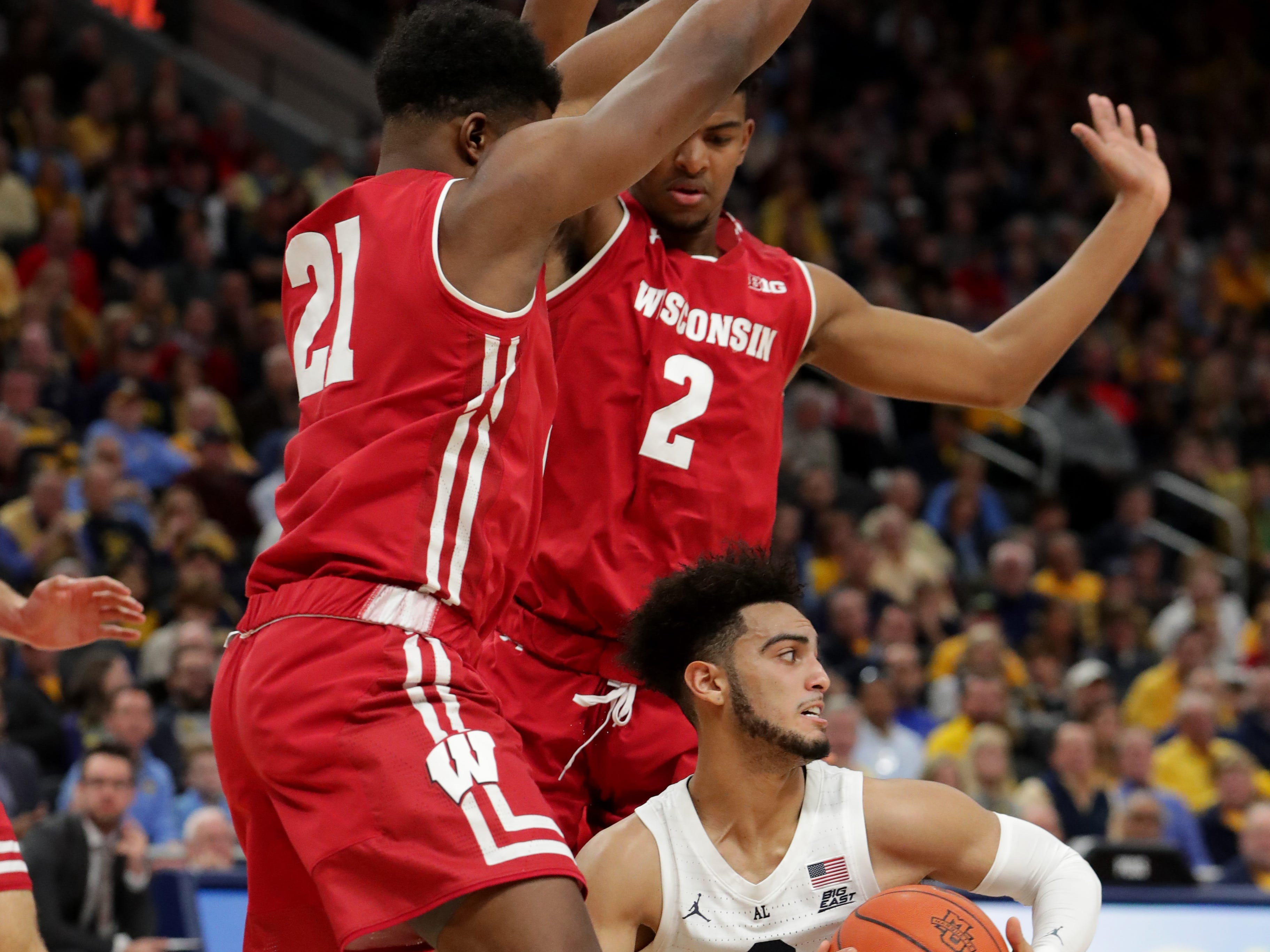Marquette guard Markus Howard finds no room while being defended by Wisconsin guard Khalil Iverson (21) and forward Aleem Ford.