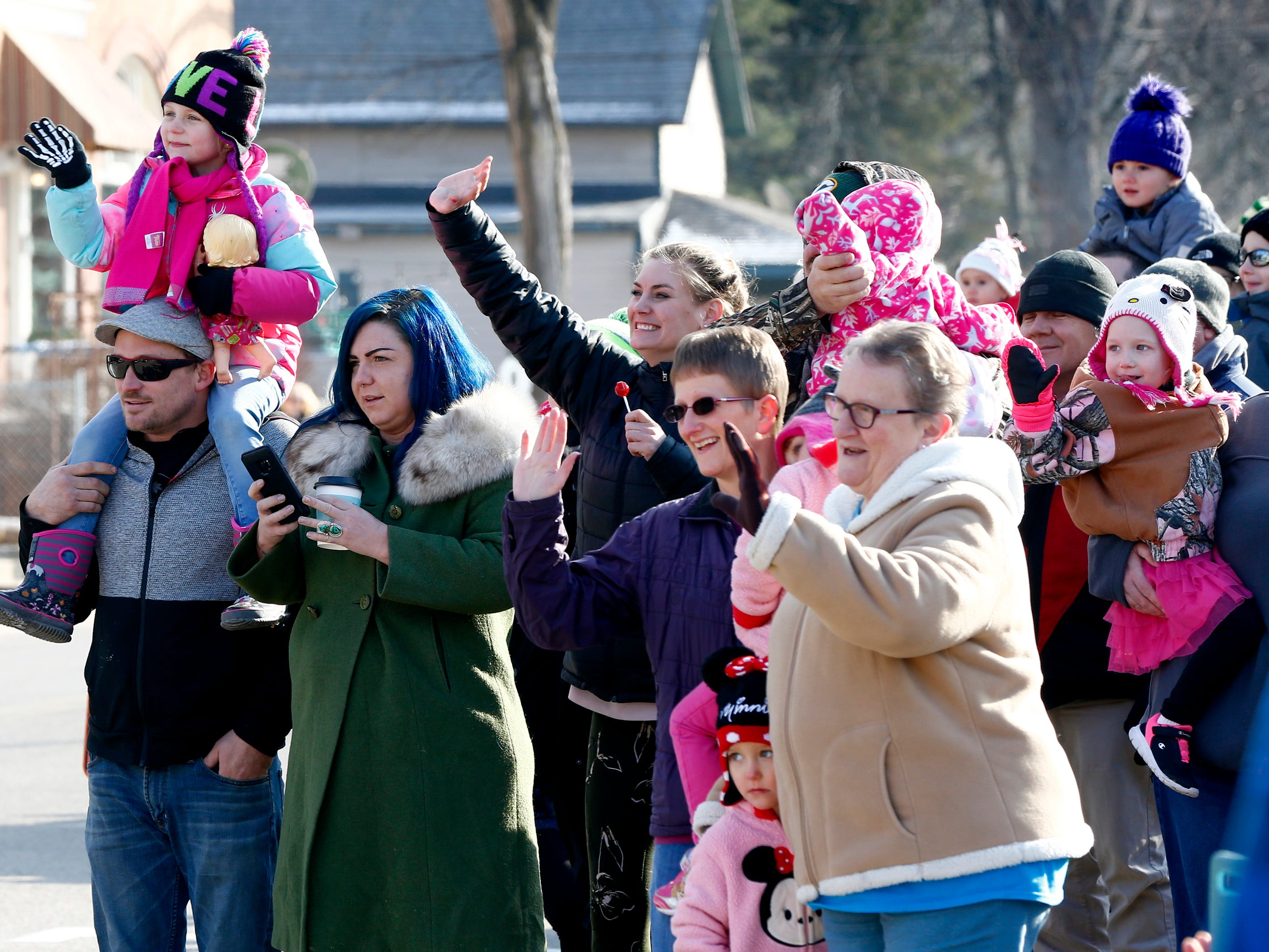 Families wave as Santa rolls to a stop at the Village Hall aboard a Wales Fire Department engine for Christmas in Wales on Dec. 8.