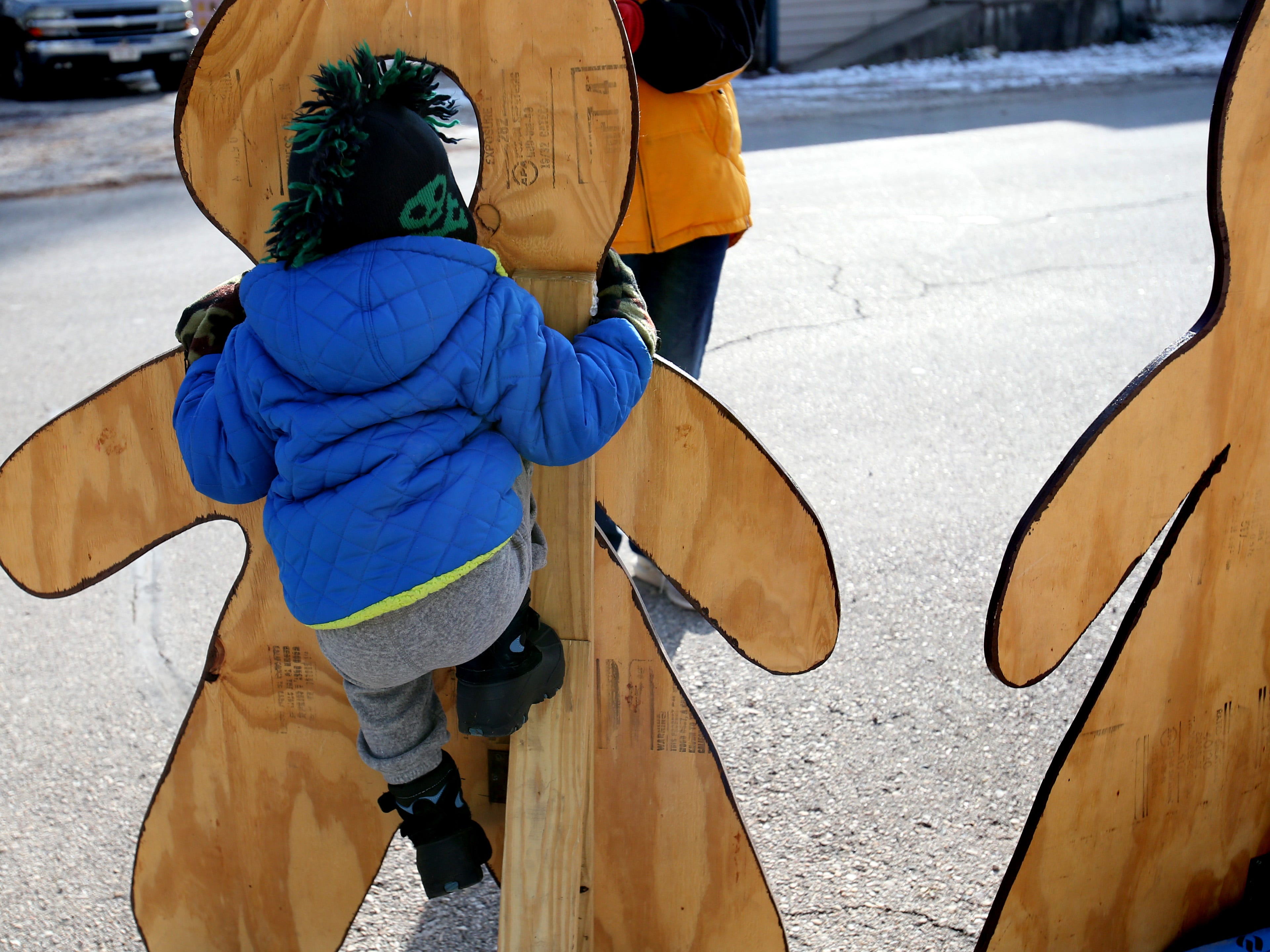Marshall Witek, 4, pulls himself up int a face cutout for a photograph during Christmas in Wales on Dec. 8.