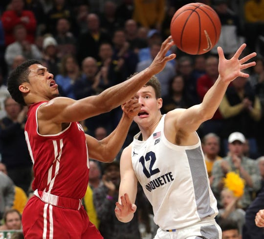 Wisconsin guard D'Mitrik Trice (left) tries to get the ball around Marquette center Matt Heldt.