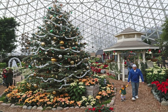 """Kyle Chick (right) of Rochester walks with his daughter Anna, and his wife Jenny Chick at the Mitchell Park Domes' """"Scrooooge!"""" holiday floral show."""