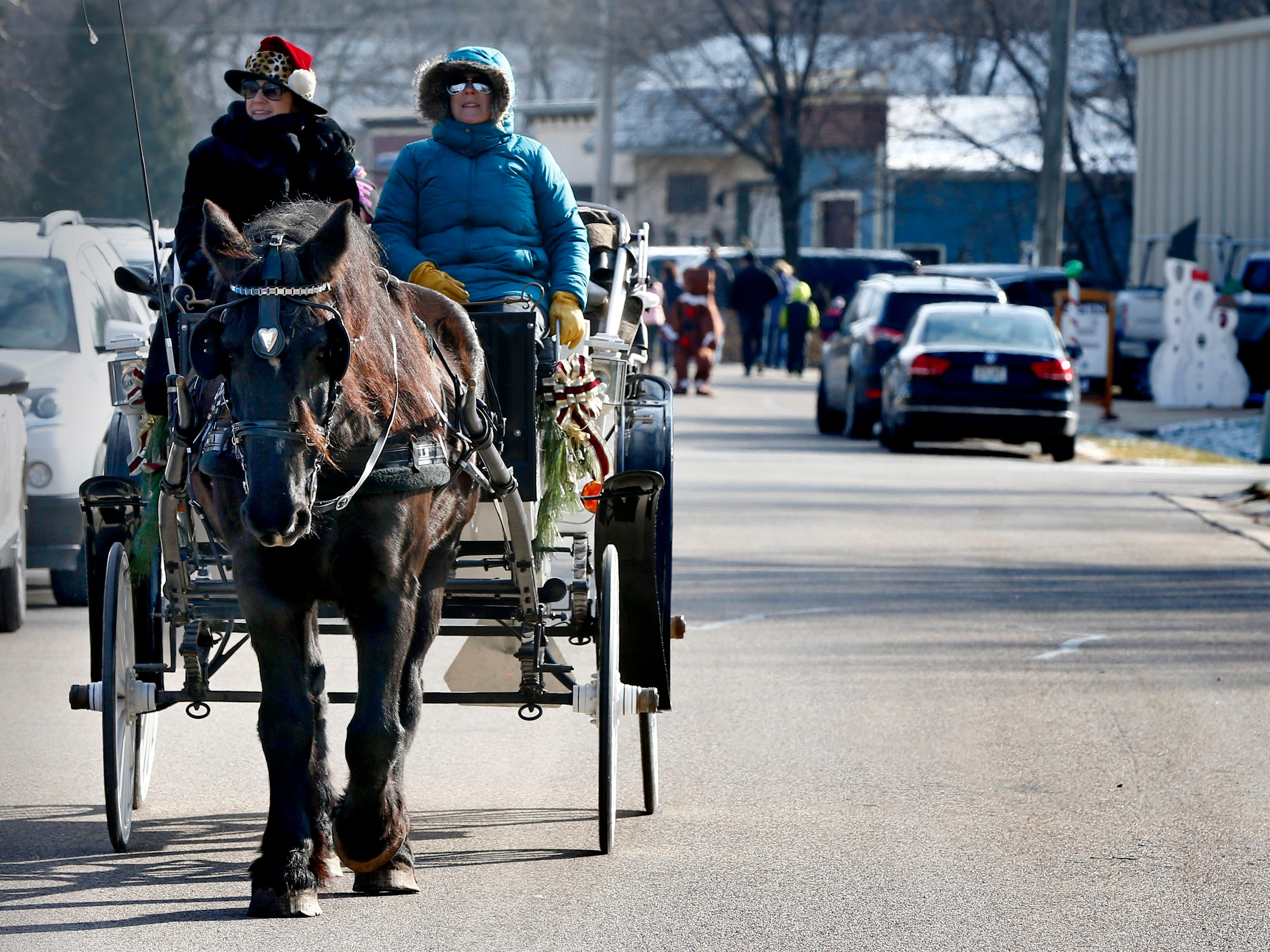 A horse-drawn carriage rolls along James Street offering visitors rides during Christmas in Wales on Dec. 8.