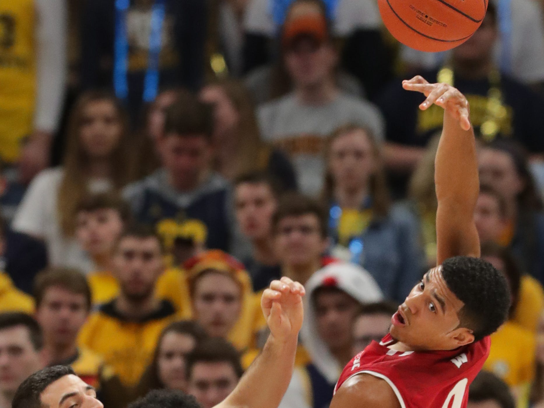 Wisconsin guard D'Mitrik Trice (0) flicks a pass to guard Khalil Iverson.