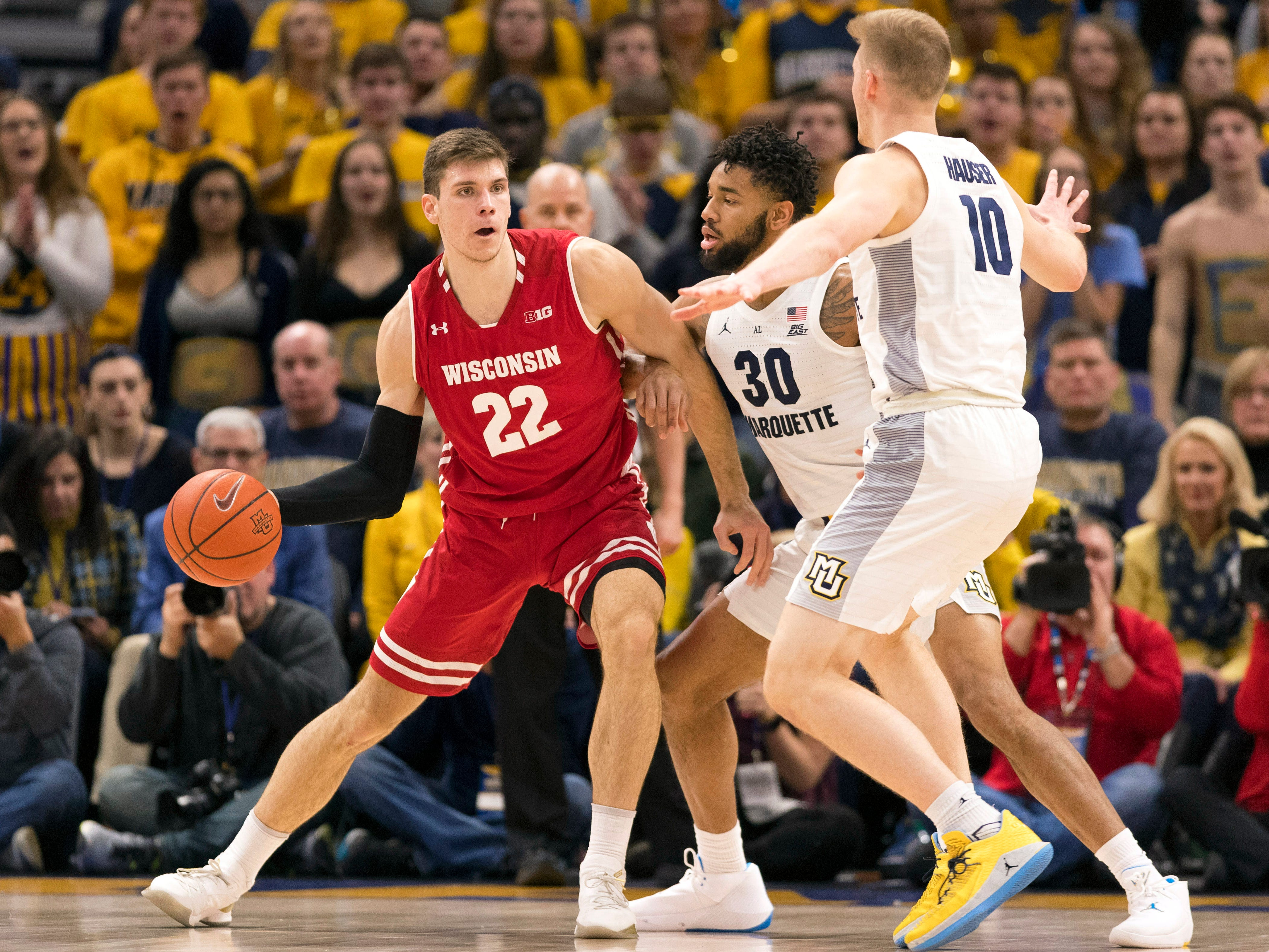 Wisconsin forward Ethan Happ looks to pass under pressure from Marquette forwards Ed Morrow (30) and Sam Hauser.