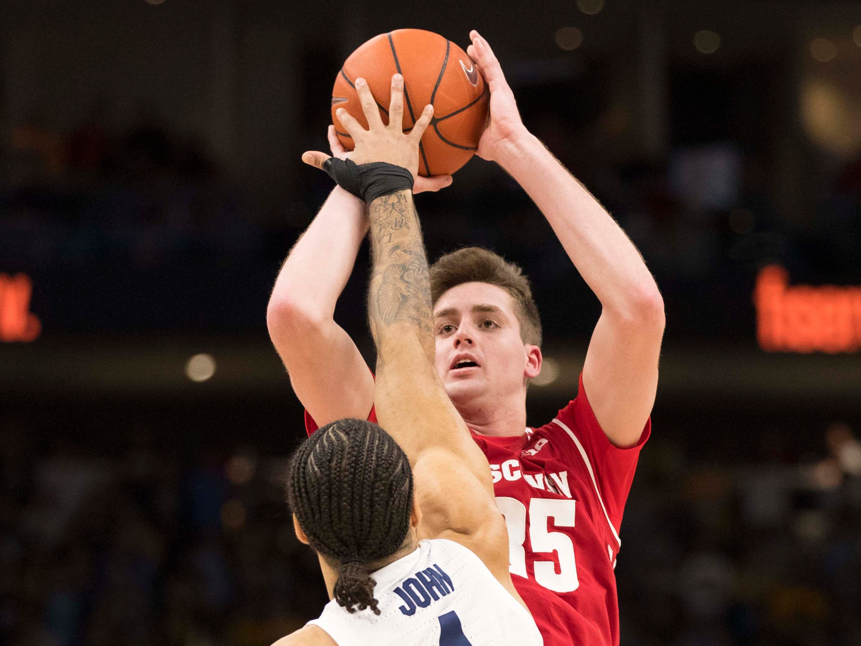 Wisconsin Badgers forward Nate Reuvers shoots against Marquette Golden Eagles forward Theo John.