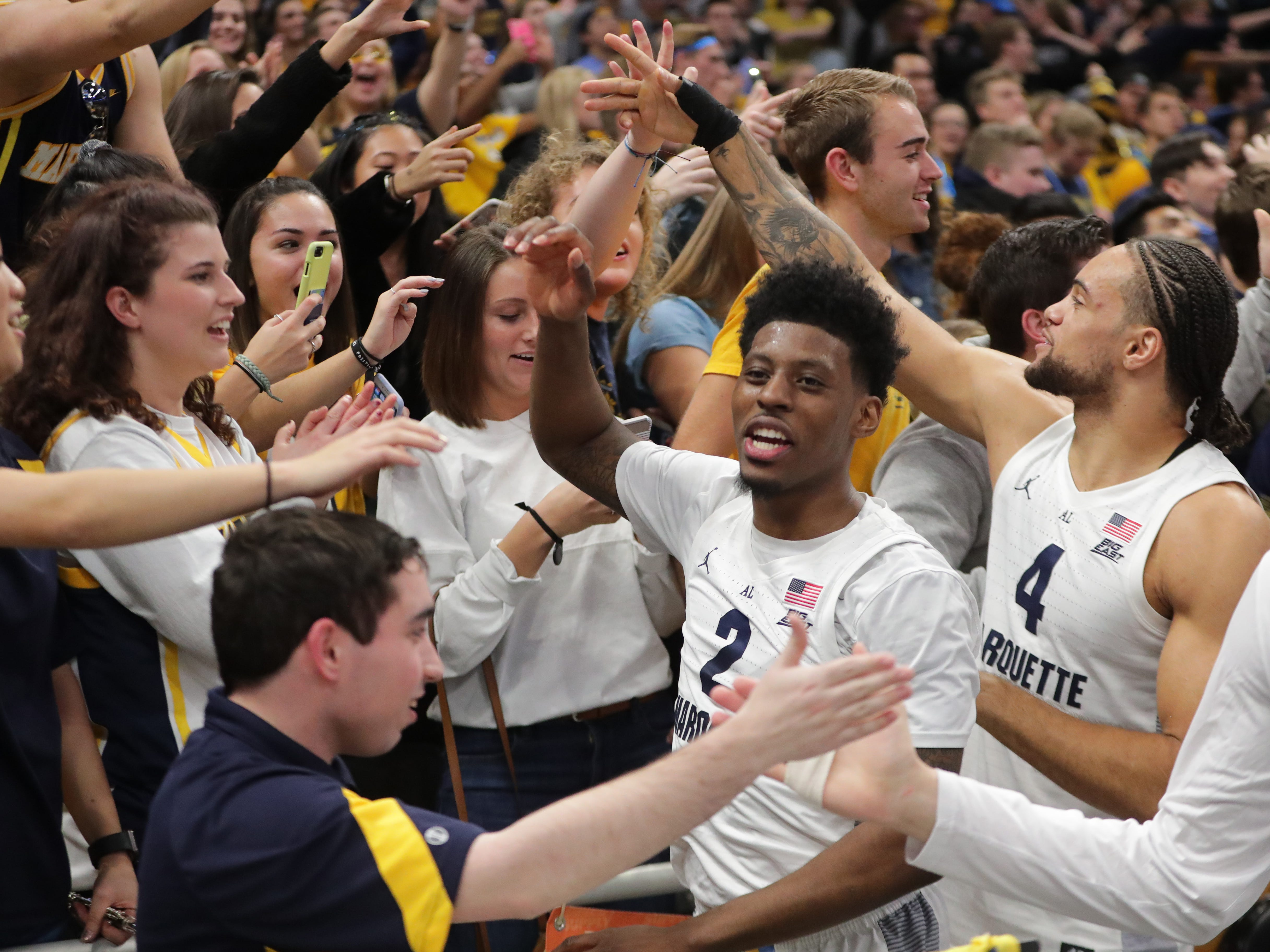 Marquette forward Sacar Anim (2) and forward Theo John celebrate with fans after the game at Fiserv Forum.