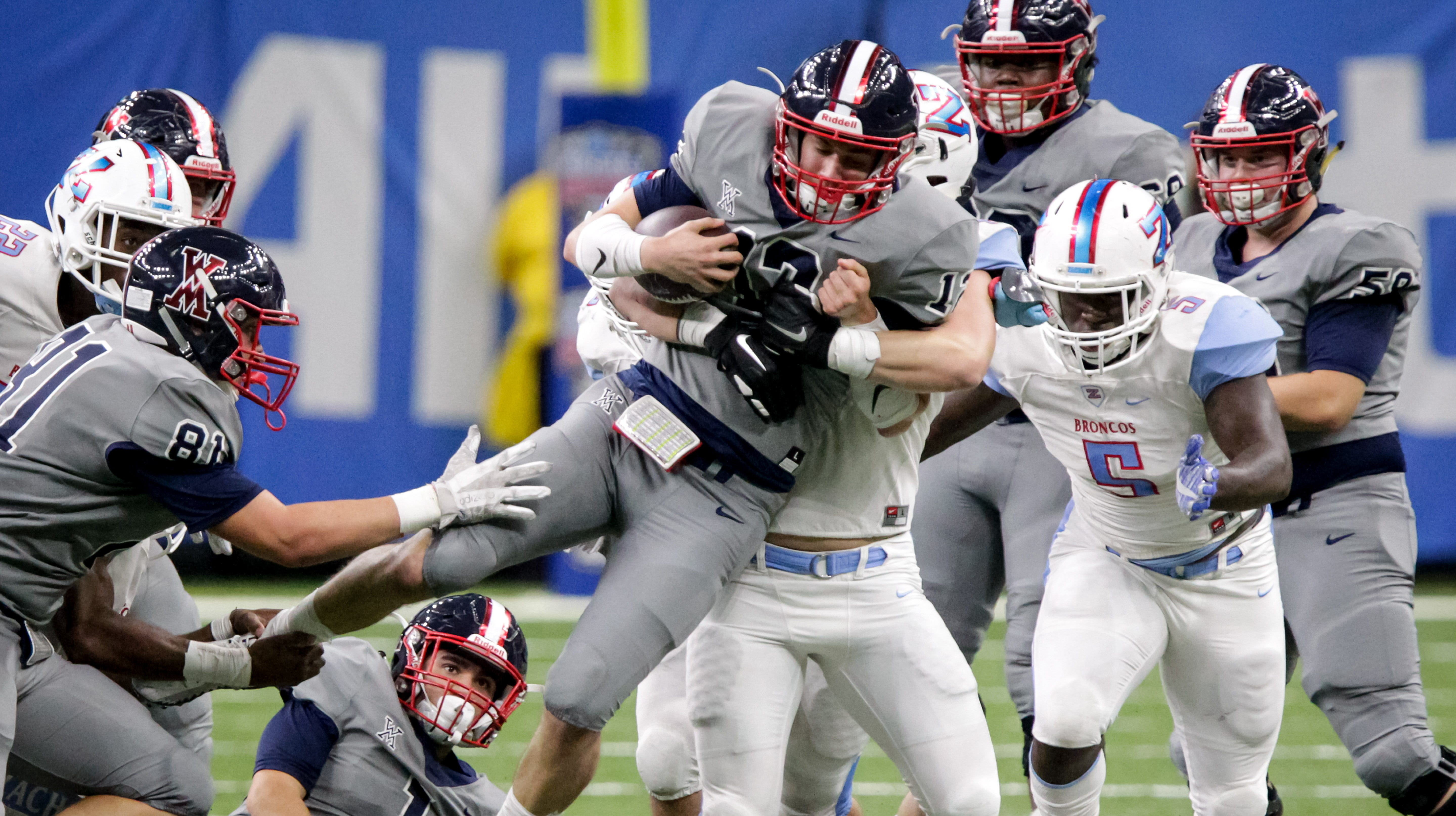 West Monroe's Garrett Kahmann (12) is tackled by Zachary's Maverick Mcclure (44) and Zachary's Cedric Brown (5) during the first half of the Class 5A championship Saturday, Dec. 8, 2018, at the Mercedes-Benz Superdome in New Orleans.