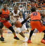 Auburn guard Jared Harper (1) runs between Dayton guard Dwayne Cohill (35) and guard Jalen Crutcher (10) for a shot at Auburn Arena on Dec. 8, 2018.
