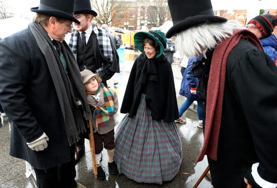 Alan Corry, left, his wife, Carla, and Andrew Nixon, 6, as Oliver Twist, spend time during the Dickens of a Christmas on Dec. 8, 2018, in Franklin.