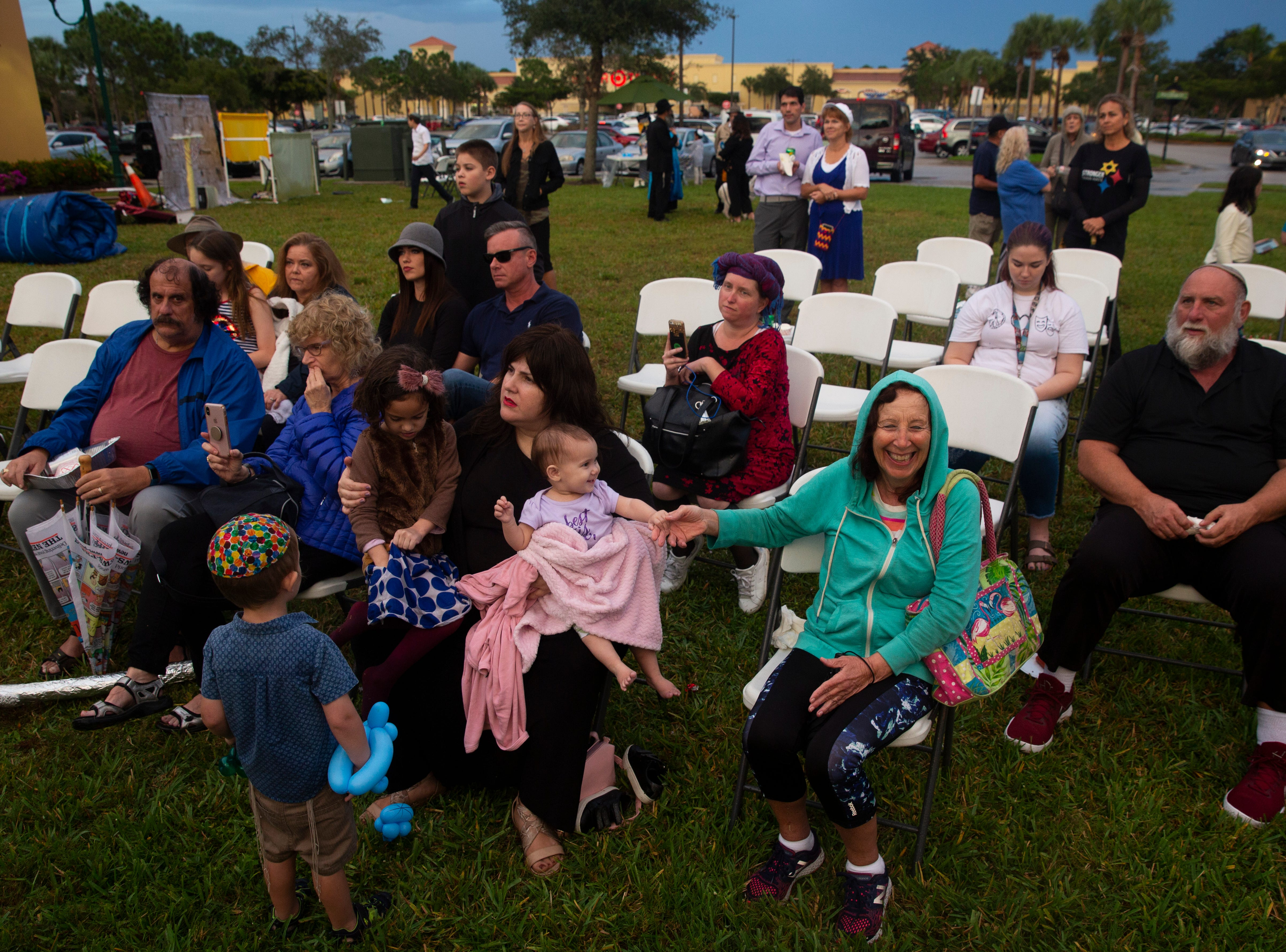 Stella Gangel, right foreground, smiles as Rabbi Mendy Greenberg, of Chabad of Bonita Springs, Estero & FGCU, prepares to light the 9-foot menorah on a rainy Sunday evening, Dec. 9, 2018, at Coconut Point in Estero to celebrate the last night of Hanukkah.