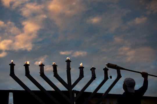 Shlomi Negri, of Estero, lights the 9-foot menorah at dusk during the celebrations hosted by the Chabad of Bonita Springs, Estero & FGCU on Sunday evening, Dec. 9, 2018, at Coconut Point in Estero.
