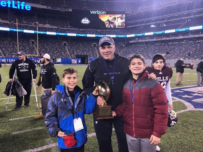 Wayne Hills football coach Wayne Demikoff and his sons, Tyler and Troy, following the bowl game win over Phillipsburg on Nov. 30 at MetLife Stadium.