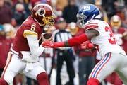 Washington quarterback Mark Sanchez attempts to avoid the sack by New York Giants free safety Curtis Riley in a December 2018 game at  FedEx Field.