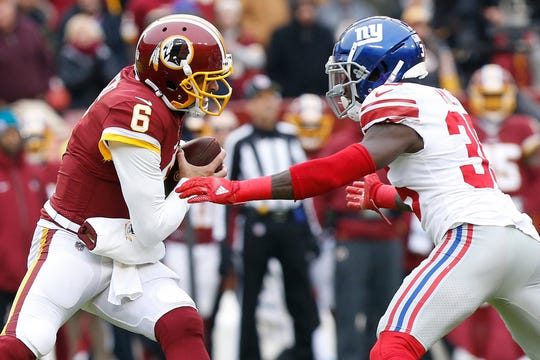 Dec 9, 2018; Landover, MD, USA; Washington Redskins quarterback Mark Sanchez (6) attempts to avoid the sack of New York Giants free safety Curtis Riley (35) in the first quarter at FedEx Field.