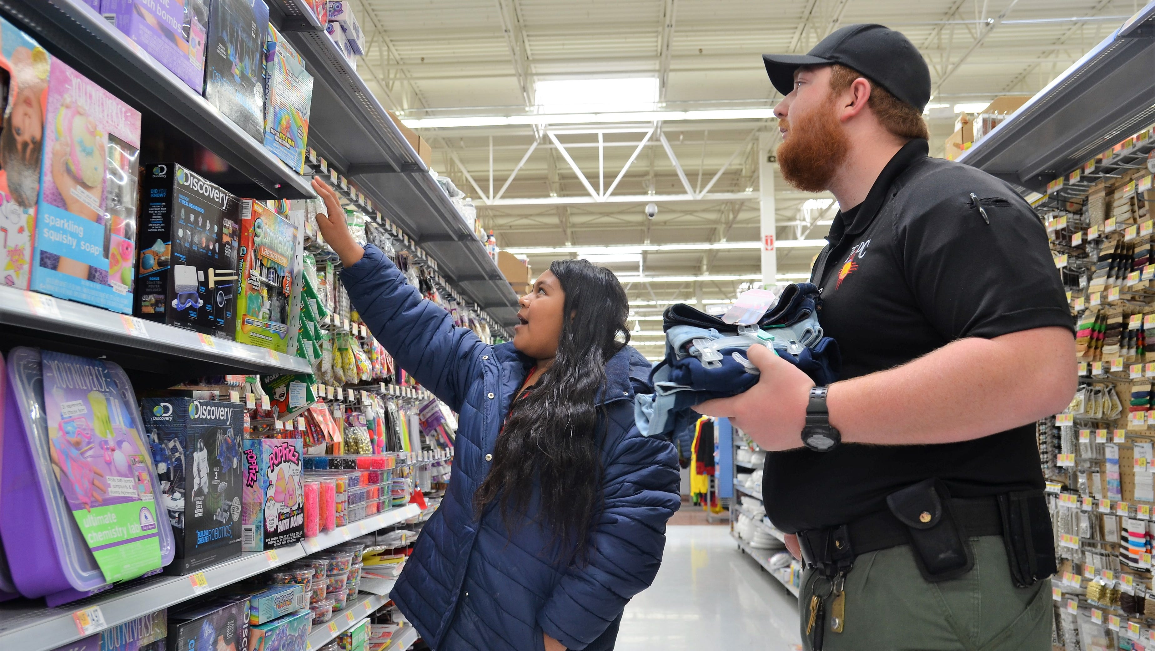 At left, Lupe Durán trying to decide which slime-making kit to get while Luna County Detention Center Officer John Vavrecan looks on during Shop with a Cop.