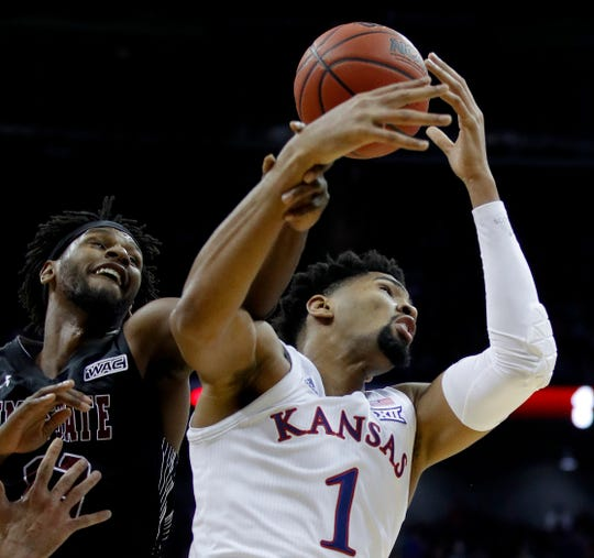 New Mexico State's C.J. Bobbitt, left, and Kansas' Dedric Lawson reach for a rebound during the first half Saturday night at the Sprint Center in Kansas City, Missouri.