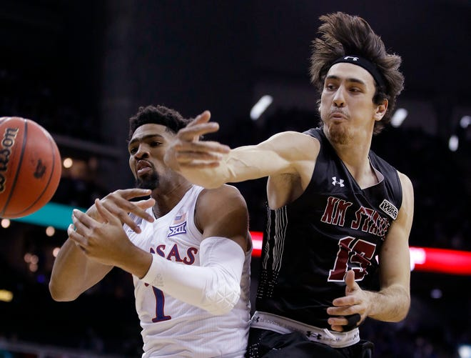 New Mexico State's Ivan Aurrecoechea, right, knocks the ball away from Kansas' Dedric Lawson (1) during the first half Saturday night at the Sprint Center in Kansas City, Missouri.