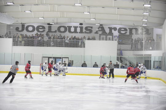 Salem and Livonia Churchill hockey players get after it Saturday at Victory Ice Center. Watching from the end zone are Salem students, sitting in the so-called Joe Louis Arena section.
