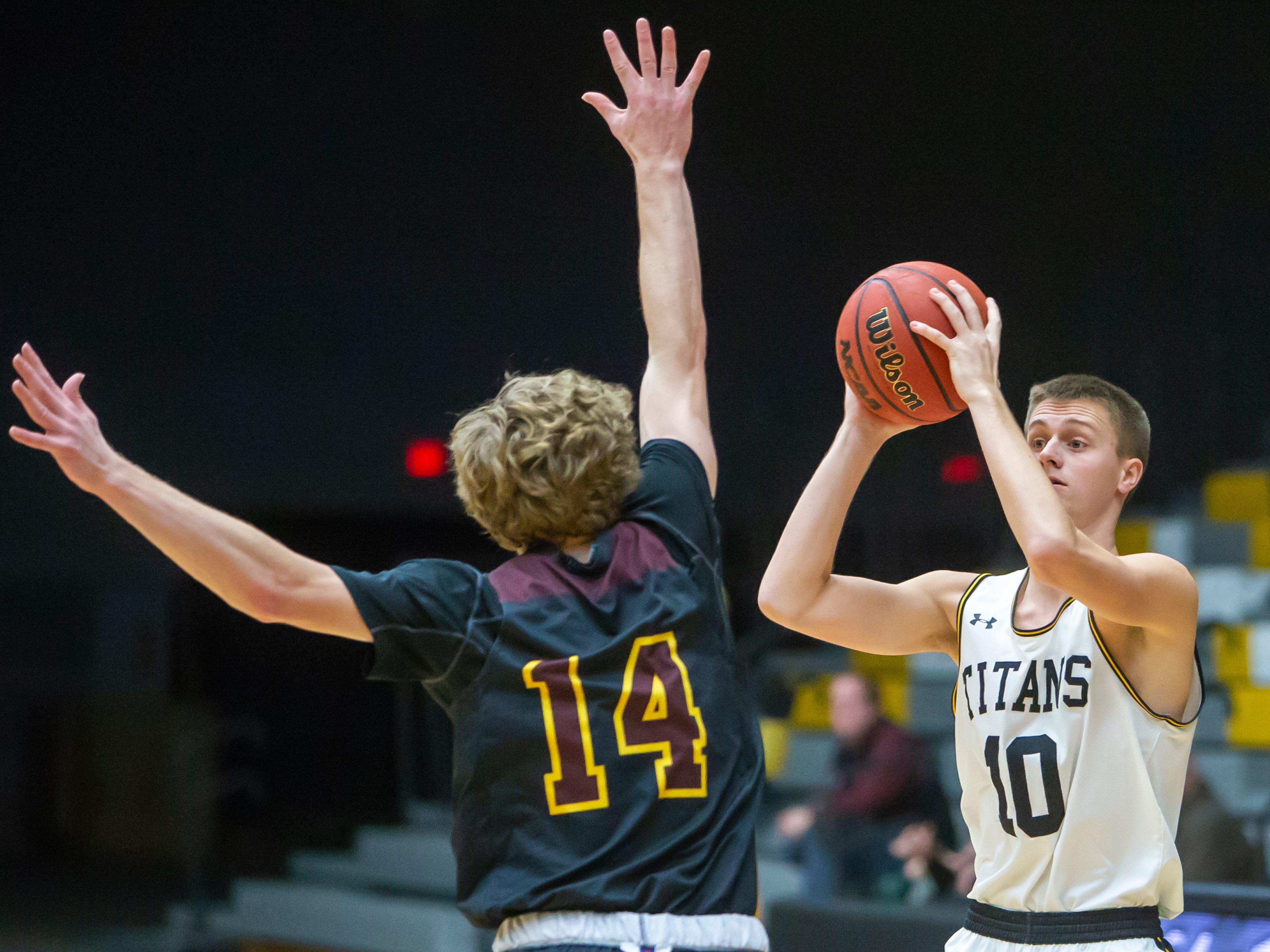 UW-Oshkosh's Jake Zeitler looks to pass the ball around Calvin's Thad Shymanski at the Kolf Sports Center on Saturday, December 8, 2018.