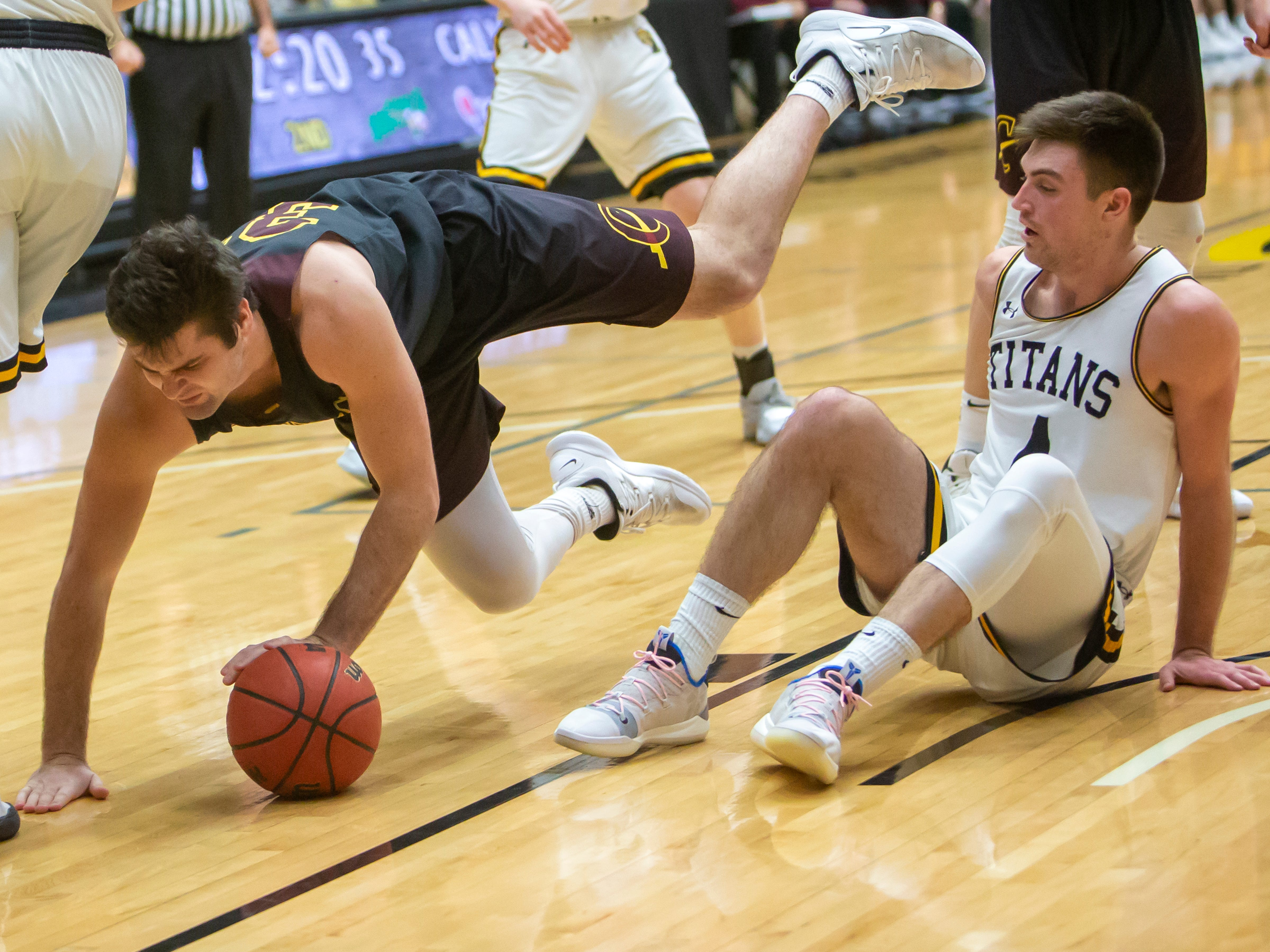 Calvin's Derrick DeVries falls during a play on the court at the Kolf Sports Center on Saturday, December 8, 2018.