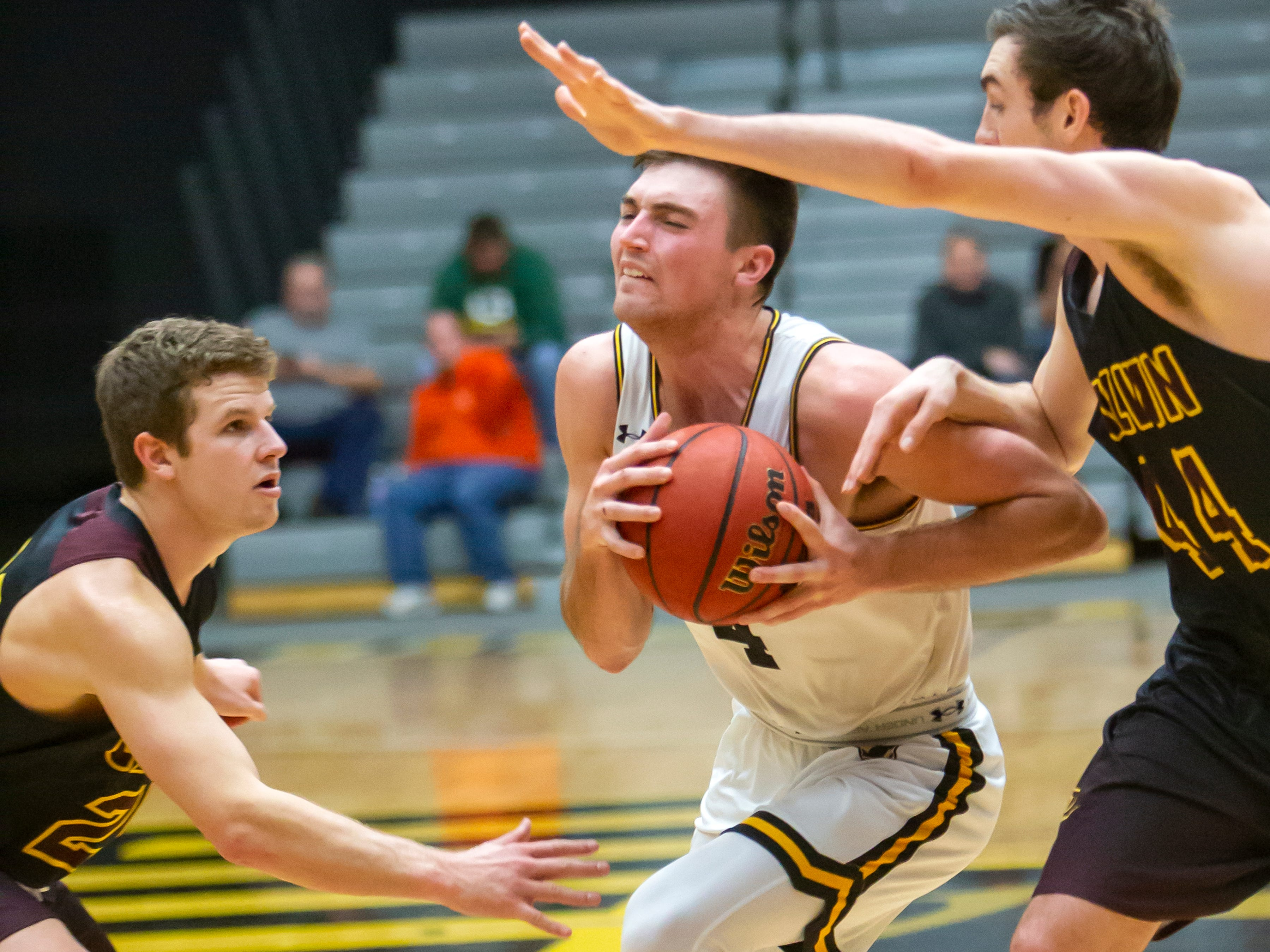UW-Oshkosh's Brett Wittchow drives the ball between Calvin blockers at the Kolf Sports Center on Saturday, December 8, 2018.