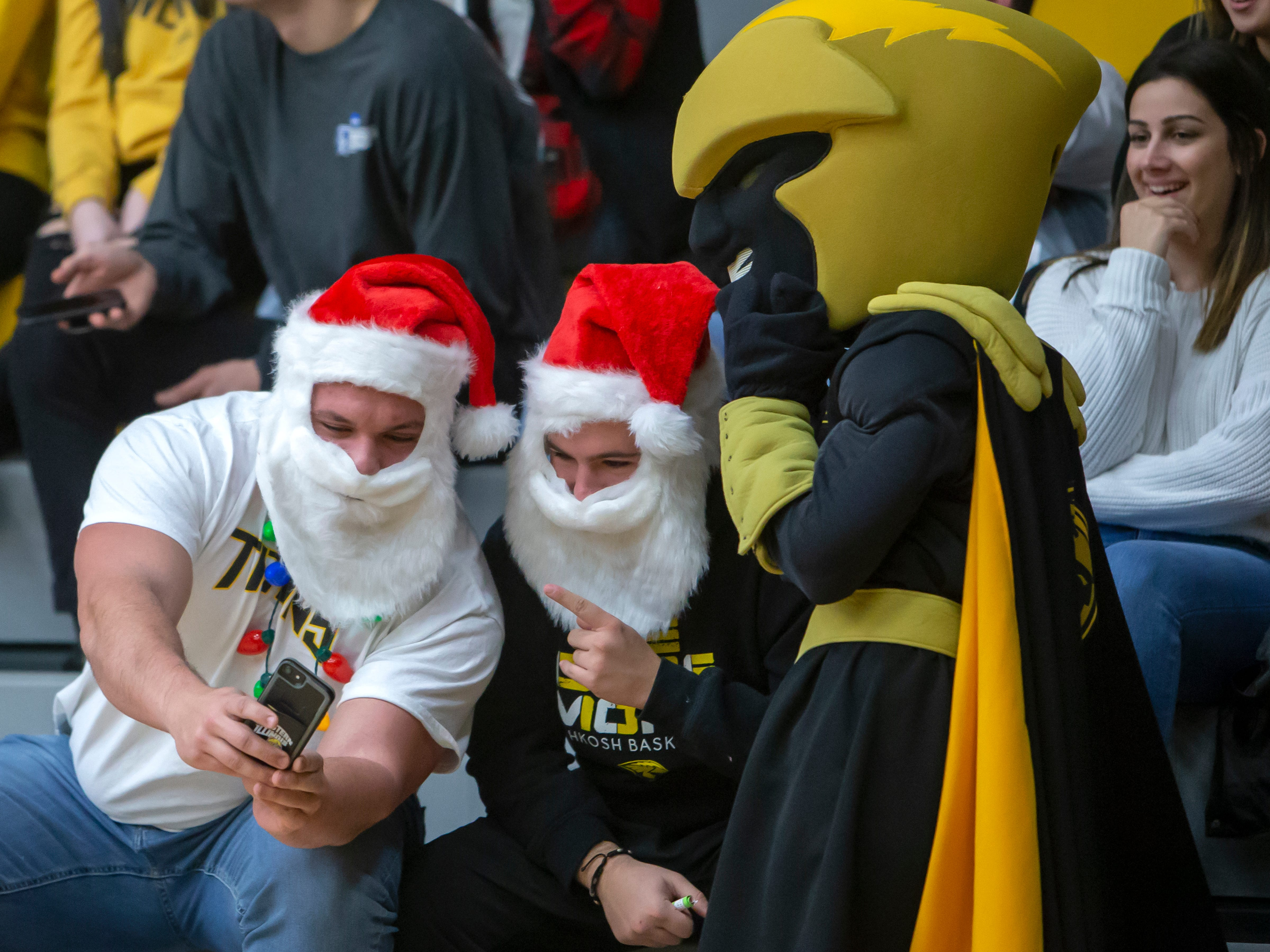 Basketball spectators wear Santa hats during the game at the Kolf Sports Center on Saturday, December 8, 2018.