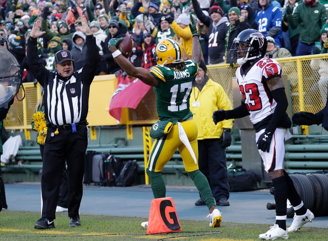 Green Bay Packers wide receiver Davante Adams (17) celebrates scoring  a touchdown against Atlanta Falcons cornerback Robert Alford (23) in the first quarter Sunday, December 9, 2018, at Lambeau Field in Green Bay, Wis.