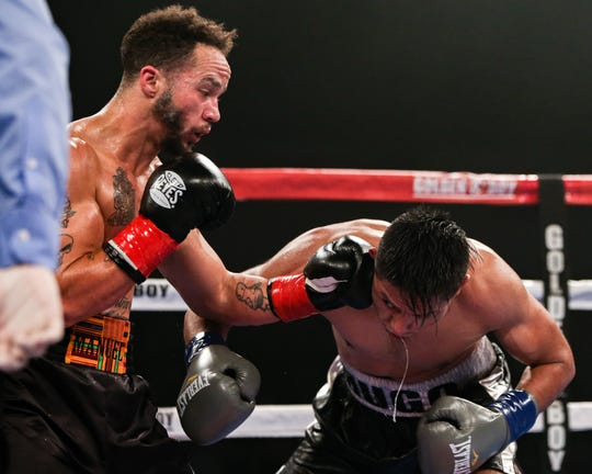 Patricio Manuel, left, lands a shot against Hugo Aguilar in the 128-pound super featherweight division bout Saturday night, Dec. 8, 2018, at Fantasy Springs Casino in Indio, California. Manuel became the first transgender male to compete as a pro boxer in the United States.