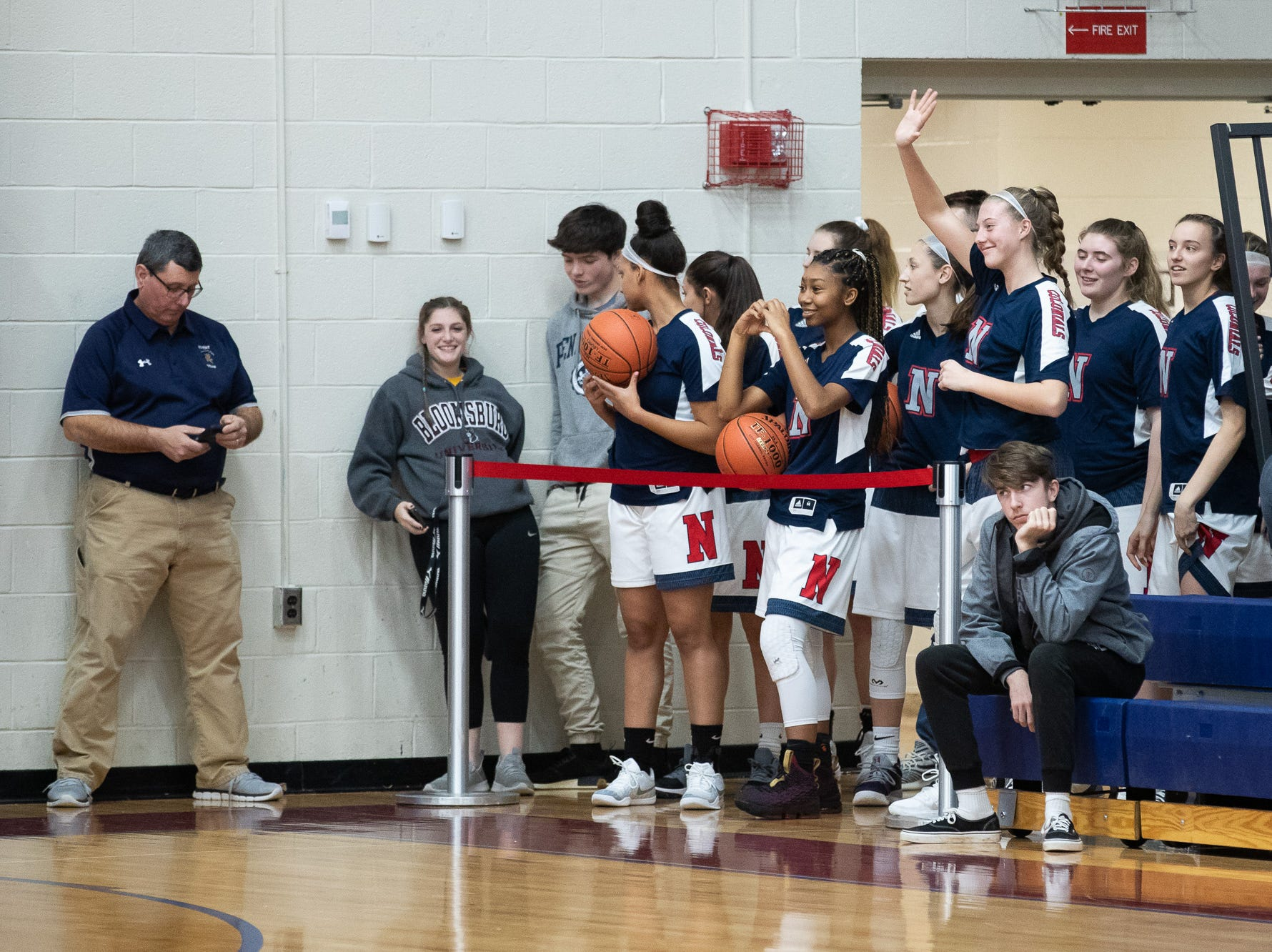 The New Oxford Lady Colonials wave to spectators while they watch the consolation game between Bermudian Springs and York Suburban during the New Oxford Girls Basketball Tip-Off Tournament, Saturday, Dec. 8, 2018, in New Oxford. The Bermudian Springs Lady Eagles defeated the York Suburban Lady Trojans 60-58.