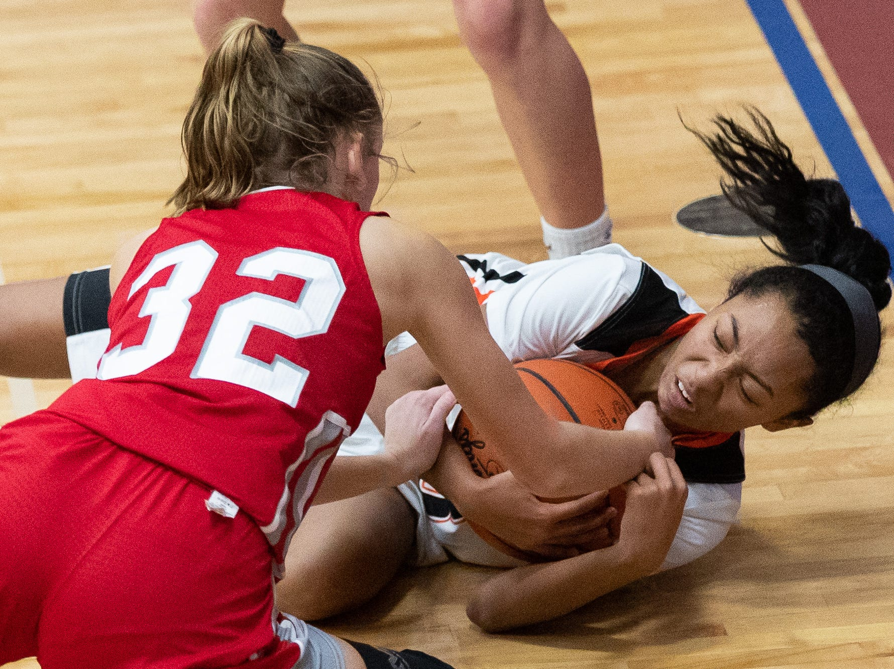 York Suburban's Kiyanna Dowling (3) wrestles with Bermudian Springs' Arden Bealmear (32) for the ball during the consolation game between Bermudian Springs and York Suburban during the New Oxford Girls Basketball Tip-Off Tournament, Saturday, Dec. 8, 2018, in New Oxford. The Bermudian Springs Lady Eagles defeated the York Suburban Lady Trojans 60-58.