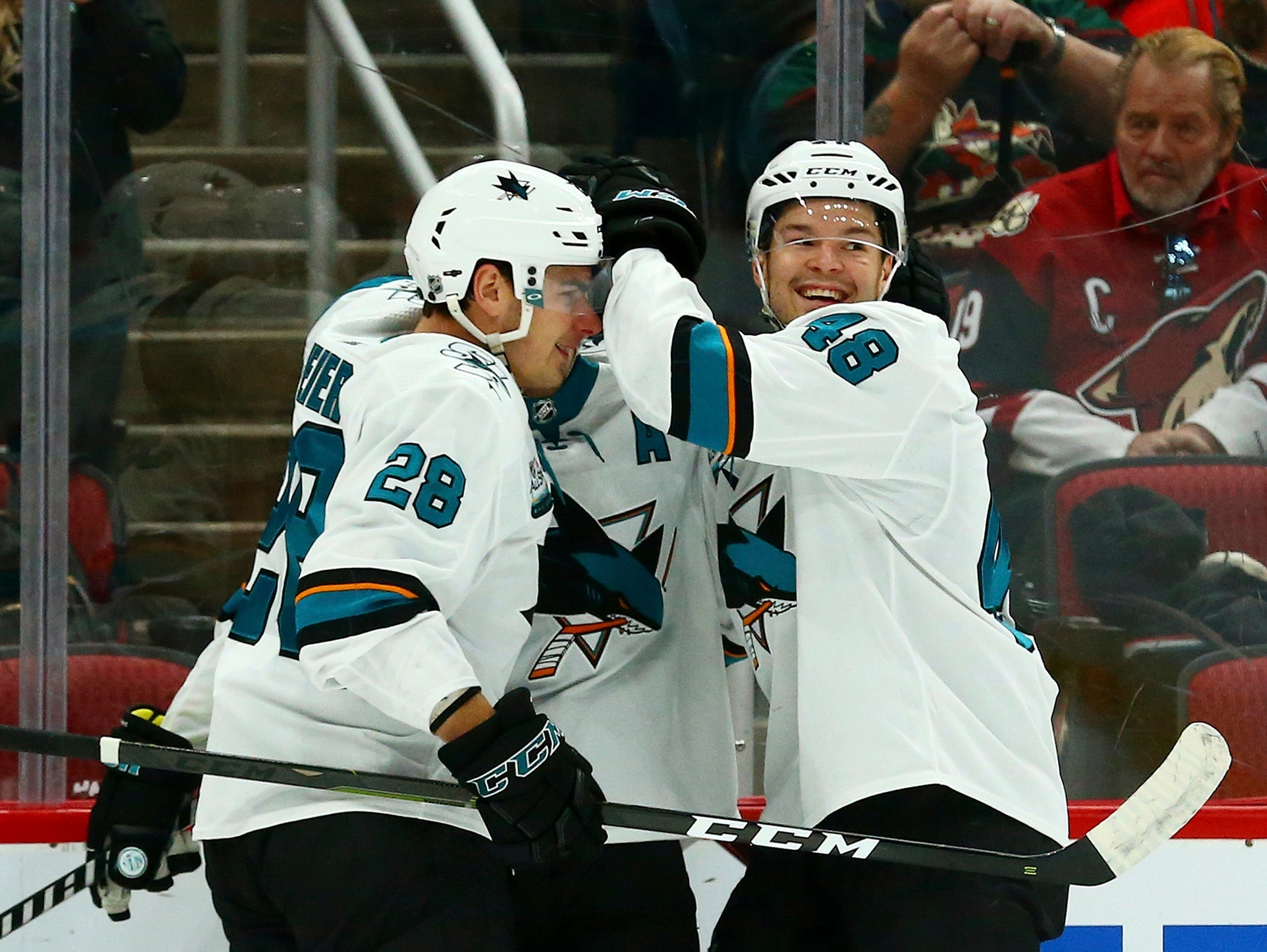 San Jose Sharks center Logan Couture, middle, celebrates his goal against the Arizona Coyotes with Sharks right wing Timo Meier (28) and center Tomas Hertl (48) during the first period of an NHL hockey game, Saturday, Dec. 8, 2018, in Phoenix.