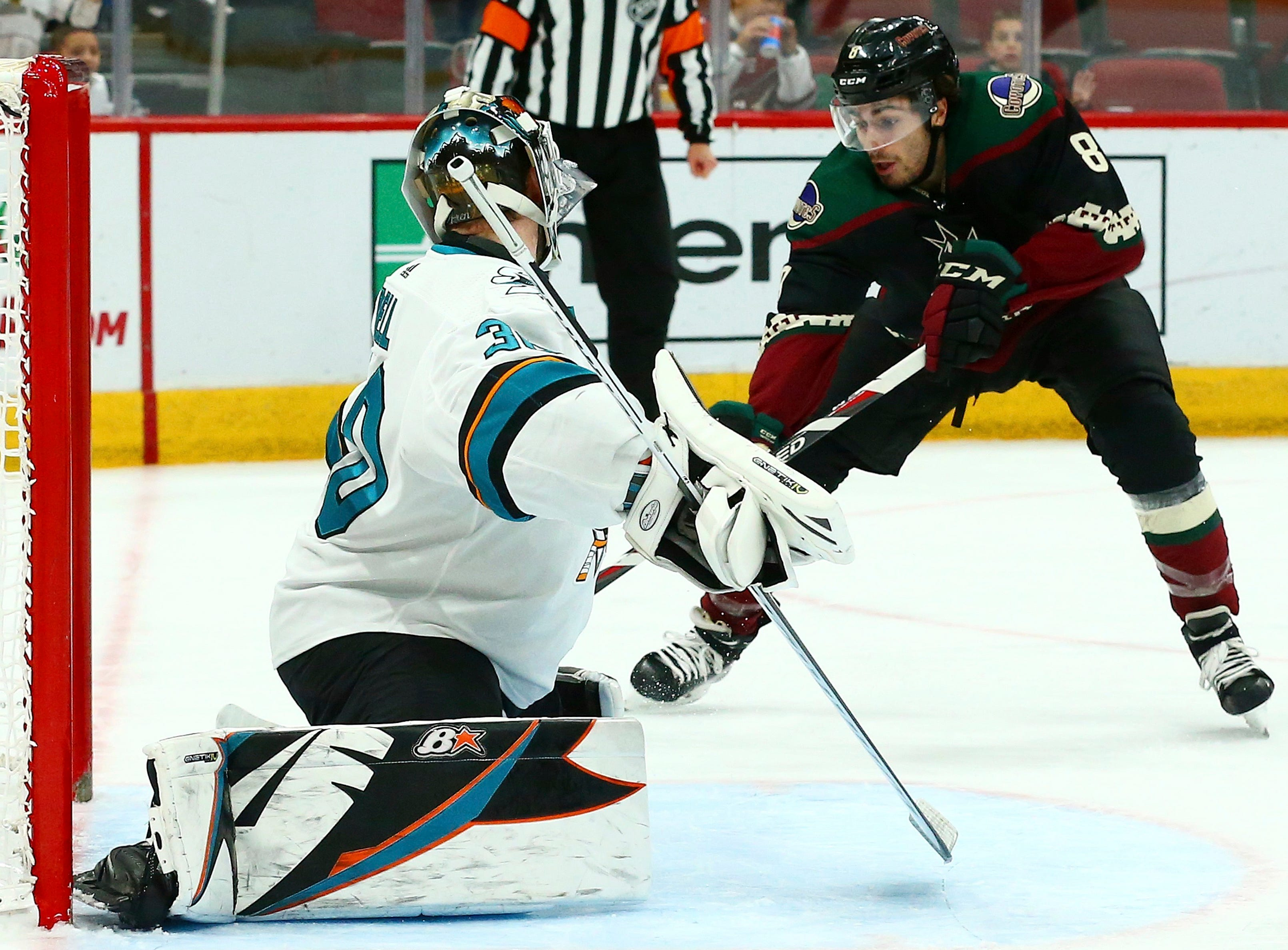 Arizona Coyotes center Nick Schmaltz (8) scores a goal against San Jose Sharks goaltender Aaron Dell, left, during the second period of an NHL hockey game, Saturday, Dec. 8, 2018, in Phoenix. (AP Photo/Ross D. Franklin)